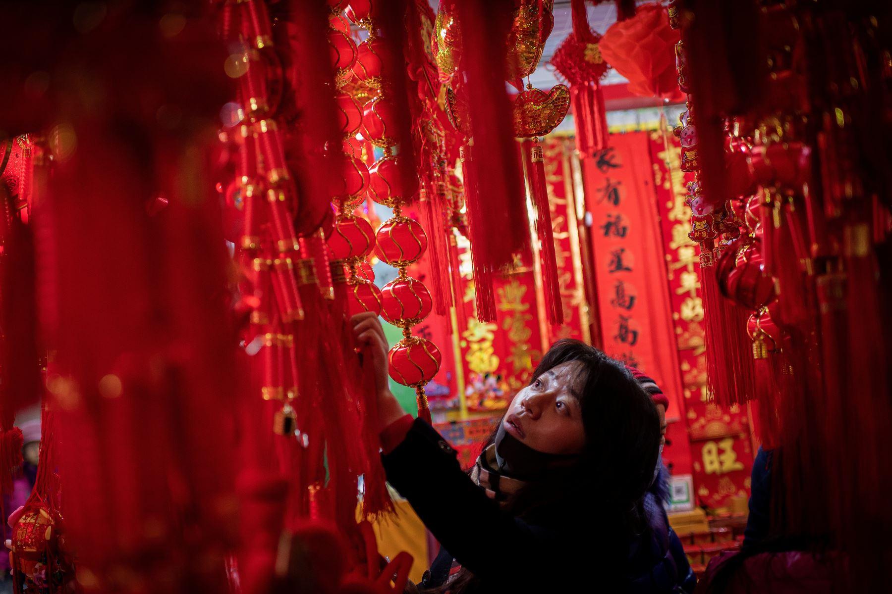 Un cliente revisa decoraciones festivas en un puesto en un mercado en Beijing antes del Año Nuevo Lunar de la Rata. Foto: AFP