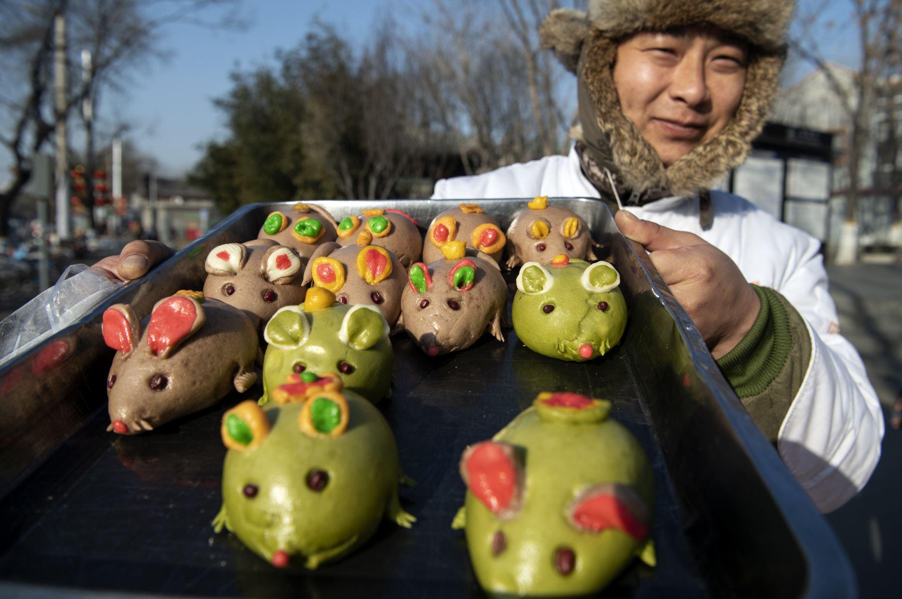 Un vendedor muestra pan en forma de rata a lo largo de una calle en Beijing, antes del Año Nuevo Lunar de la Rata. Foto: AFP
