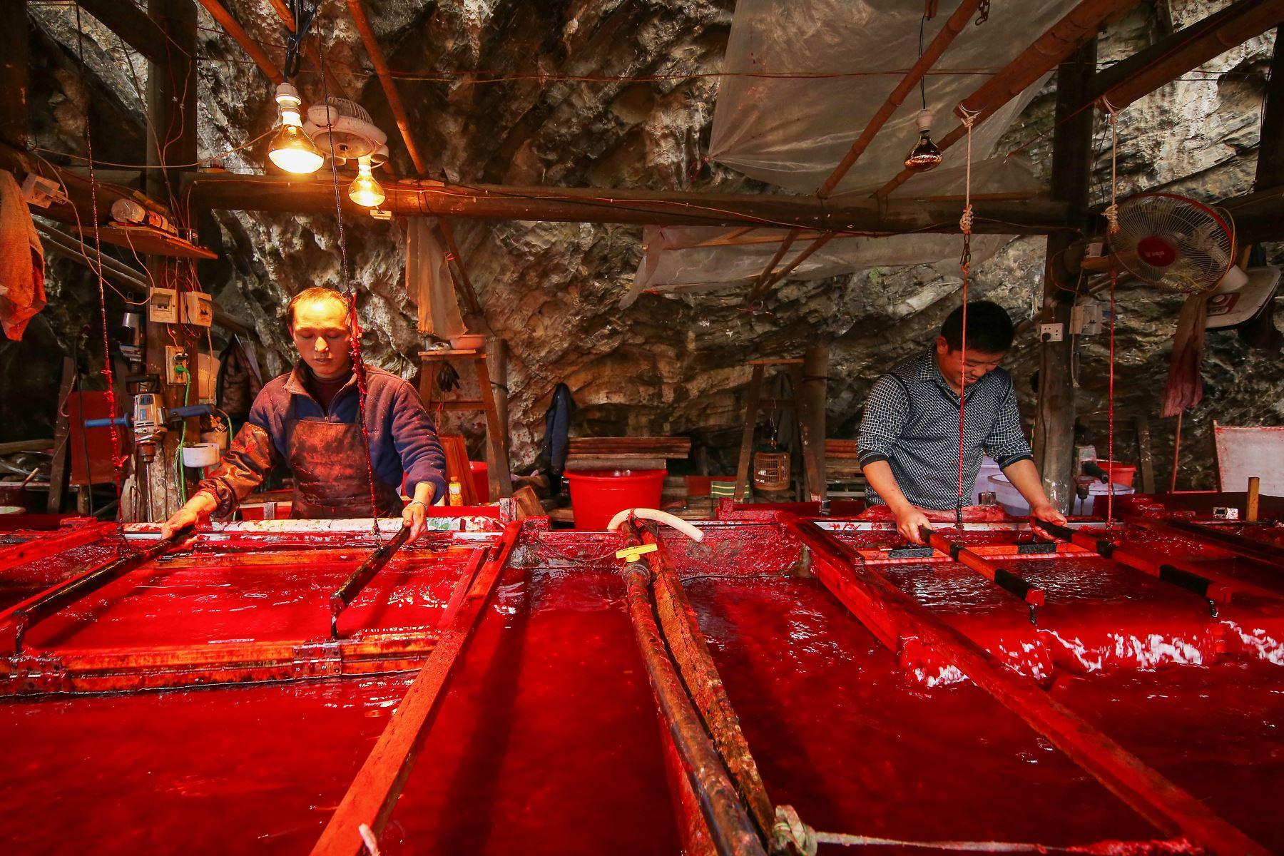 Trabajadores fabricando papel rojo para decoraciones del Año Nuevo Lunar, en Danzhai, en la provincia suroccidental china de Guizhou. Foto: AFP