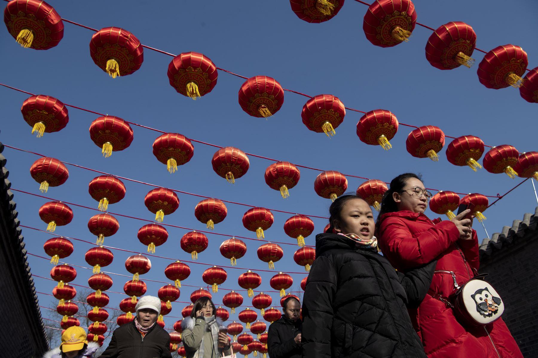 La gente camina bajo linternas chinas a lo largo de una calle en Beijing, antes del Año Nuevo Lunar de la Rata. Foto: AFP