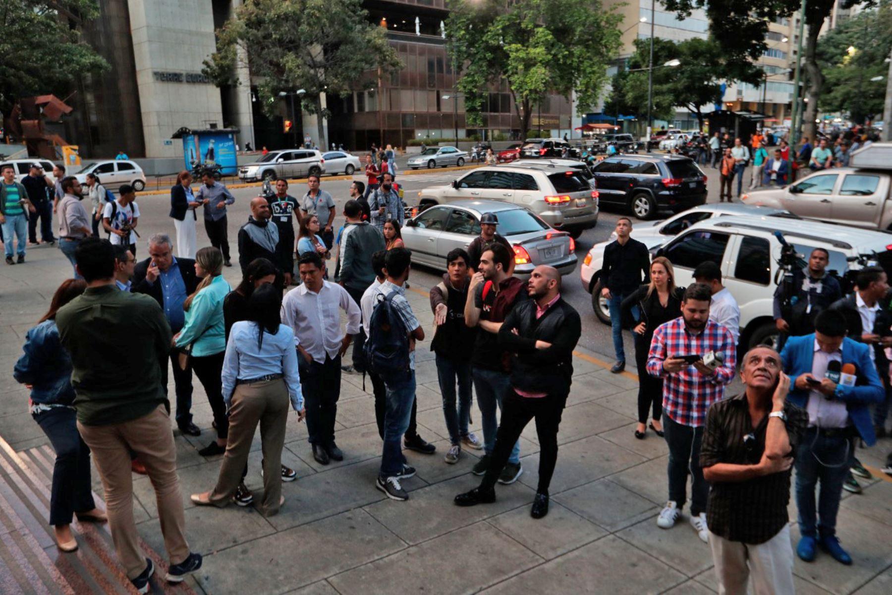 Simpatizantes de Juan Guaidó y diputados venezolanos aguardan en los alrededores del edificio donde fue allanada la oficina del líder opositor. Foto: EFE