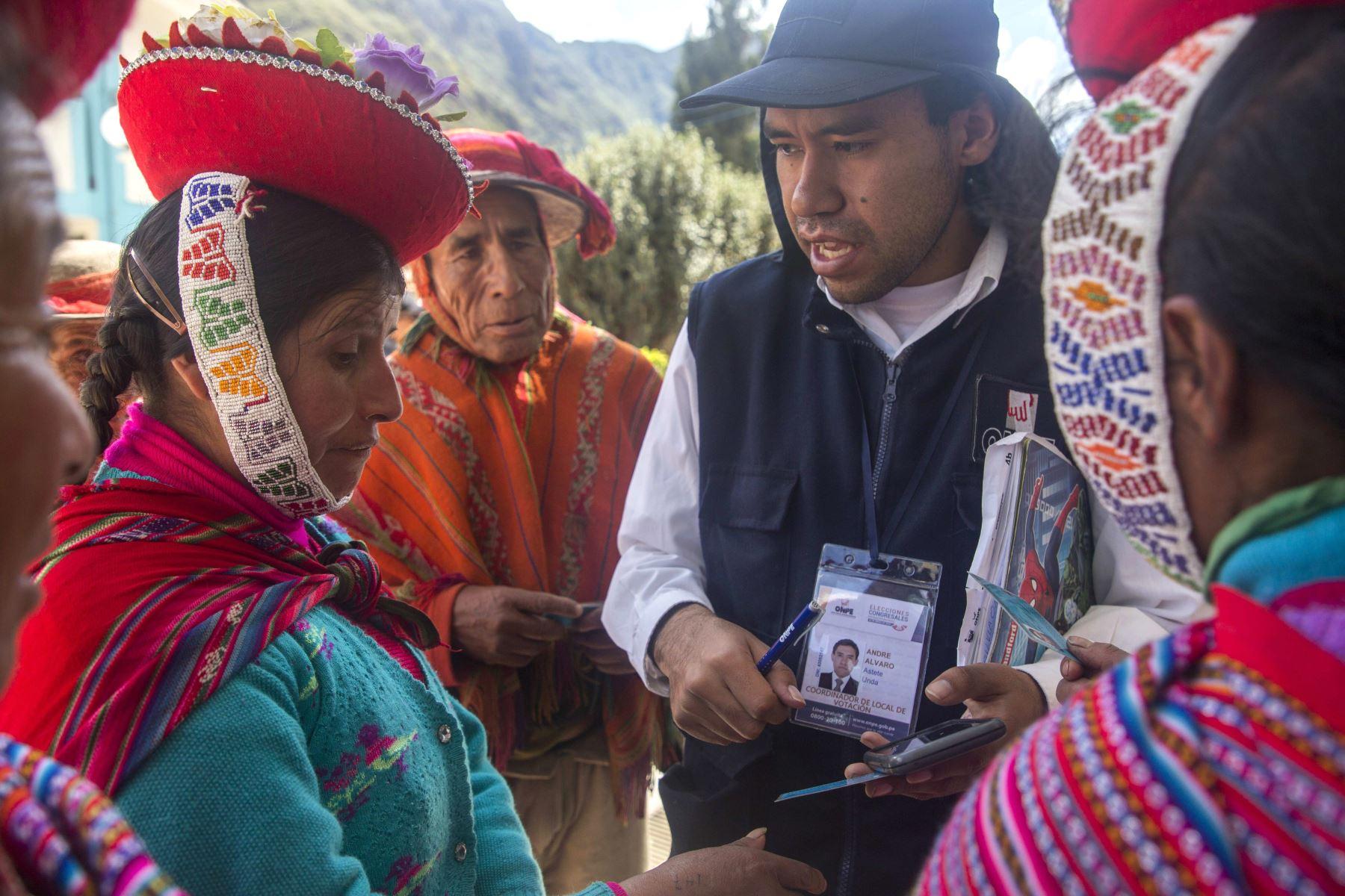 Un empleado de la Oficina Nacional de Preocesos Electorales (ONPE) ayuda a buscar las mesas de votación a integrantes de la comunidad campesina Quelccanqa  del centro poblado de Ollantaytambo en el departamento del Cuzco (Perú), donde se realizaron  elecciones extraordinarias al Congreso. Foto: EFE