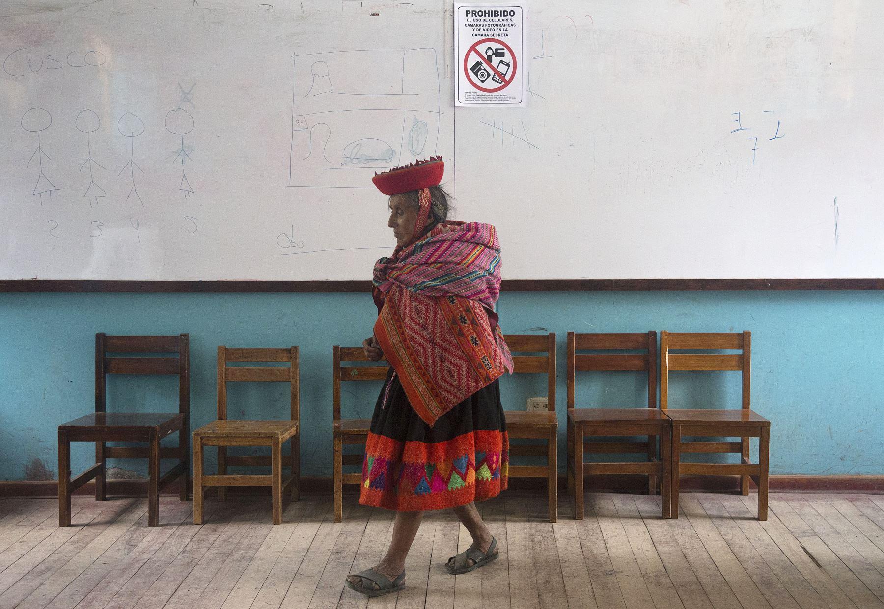 Una mujer indígena camina en un colegio electoral durante las elecciones legislativas en Ollantaytambo en la región de Cuzco. Foto: AFP