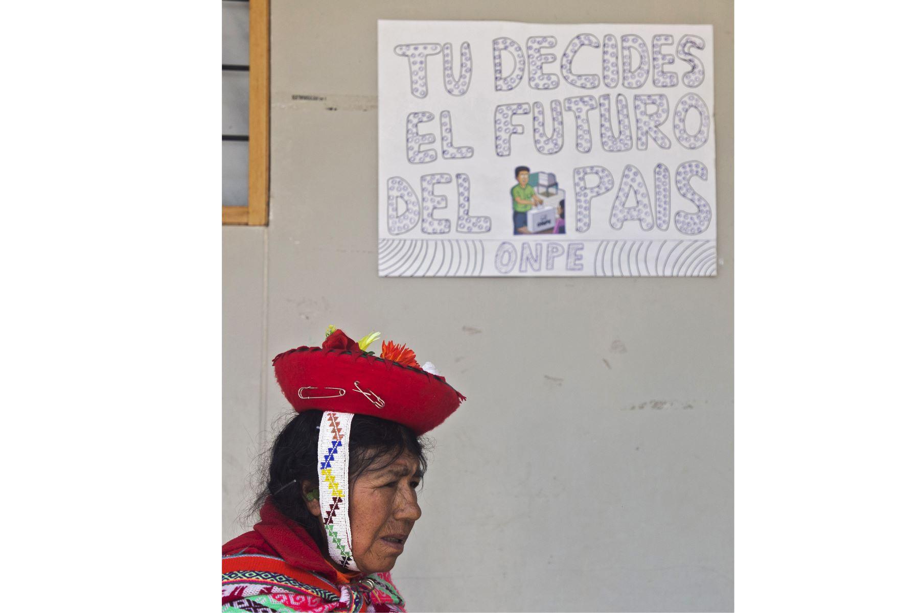 """Una mujer indígena pasa junto a un letrero que dice """"Tú decides el futuro del país"""" en un colegio electoral durante las elecciones legislativas en Ollantaytambo, en la región Cusco. Foto: AFP"""