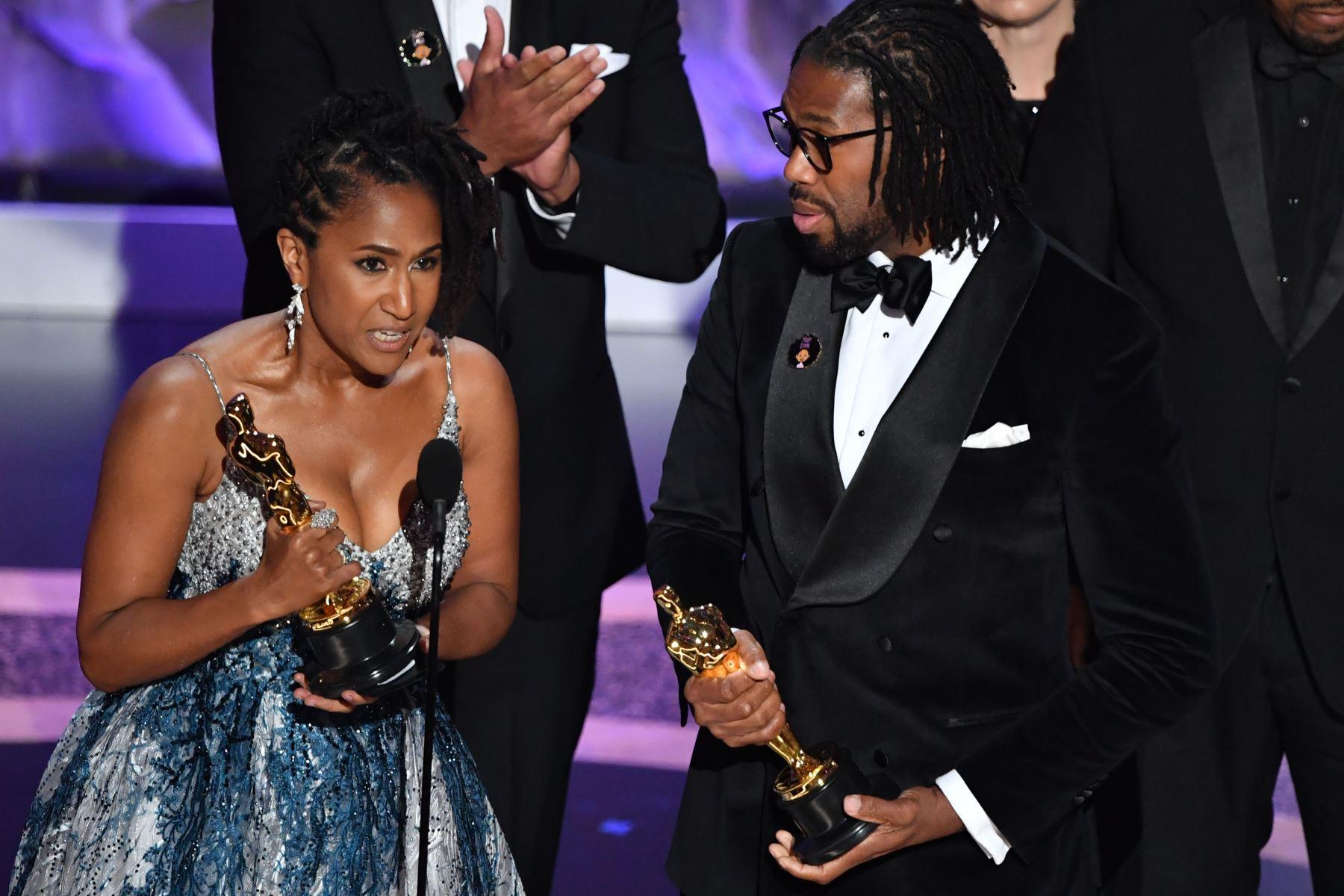 """Karen Rupert Toliver  y el director estadounidense Matthew A. Cherry aceptan el premio al Mejor Cortometraje de Animación por """"Hair Love"""" en el escenario durante la 92a edición de los Oscar en el Dolby Theatre de Hollywood, California. Foto: AFP"""