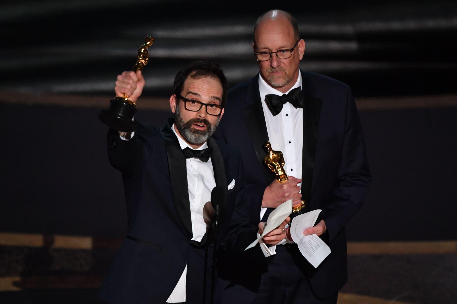 """Los editores de cine de los Estados Unidos Andrew Buckland (izq.) Y Michael McCusker aceptan el premio a la Mejor Edición de Cine por """"Ford v Ferrari"""" durante los 92o Oscars en el Dolby Theatre de Hollywood, California. Foto: AFP"""