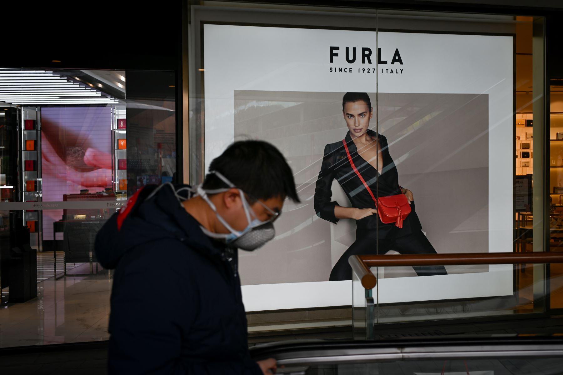 Un hombre con una máscara facial camina por un centro comercial en Beijing. Foto: AFP