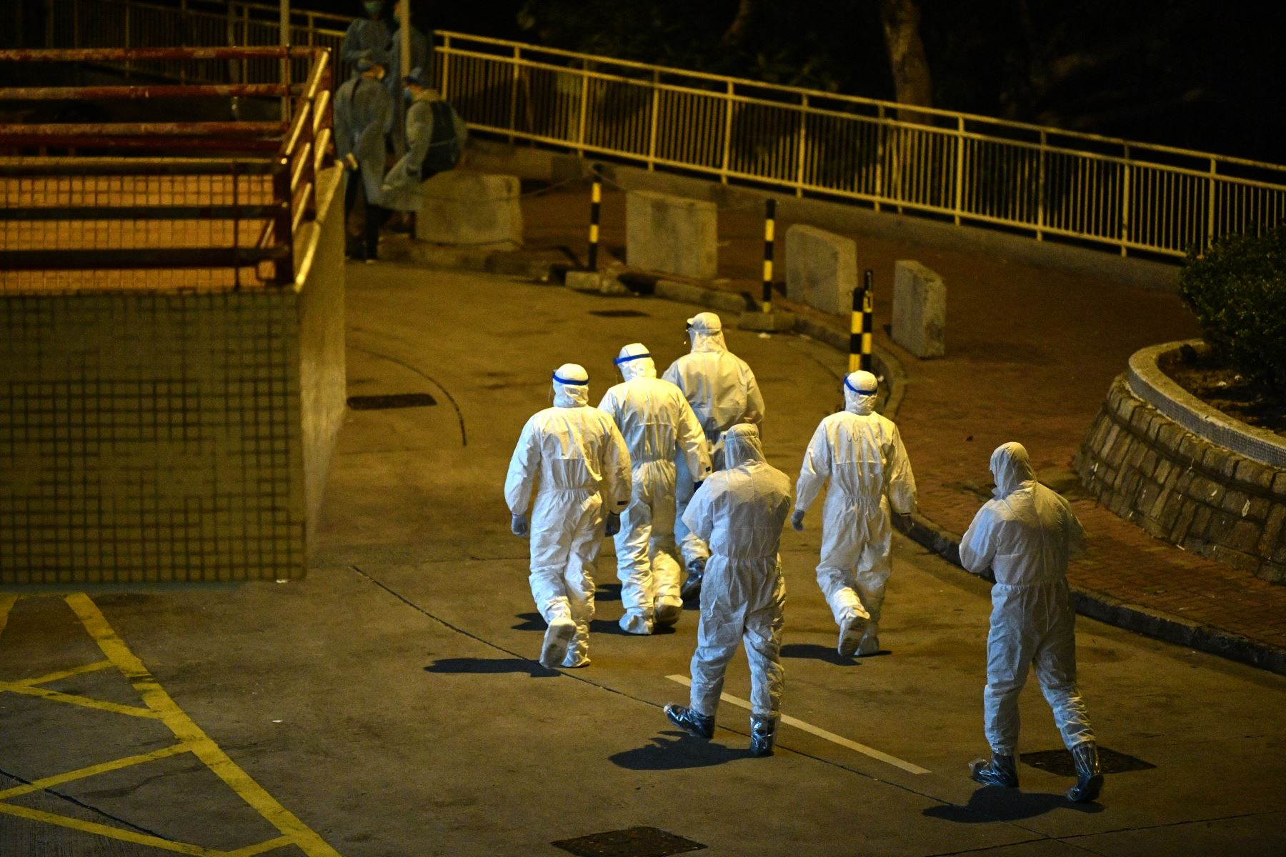 El personal médico que usa trajes protectores camina por los terrenos de una propiedad residencial en Hong Kong, tras confirmase que dos personas habían contraído el coronavirus. AFP