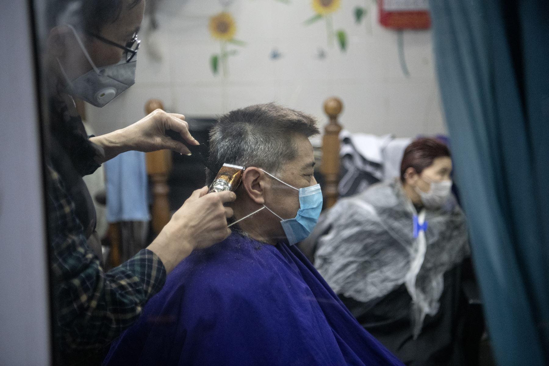 Un hombre con una máscara protectora se corta el cabello por un barbero en Shanghai . AFP
