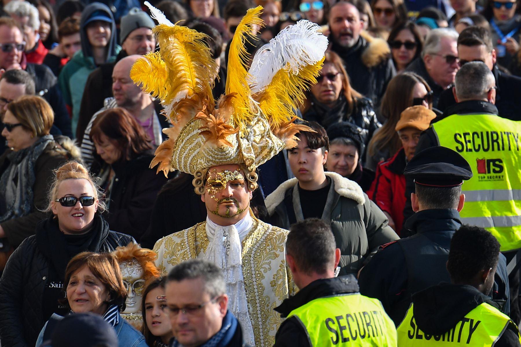 Los oficiales de seguridad  revisan a los participantes con máscaras y trajes de época que acceden a laPlaza de San Marcos durante el Carnaval de Venecia. Foto: AFP