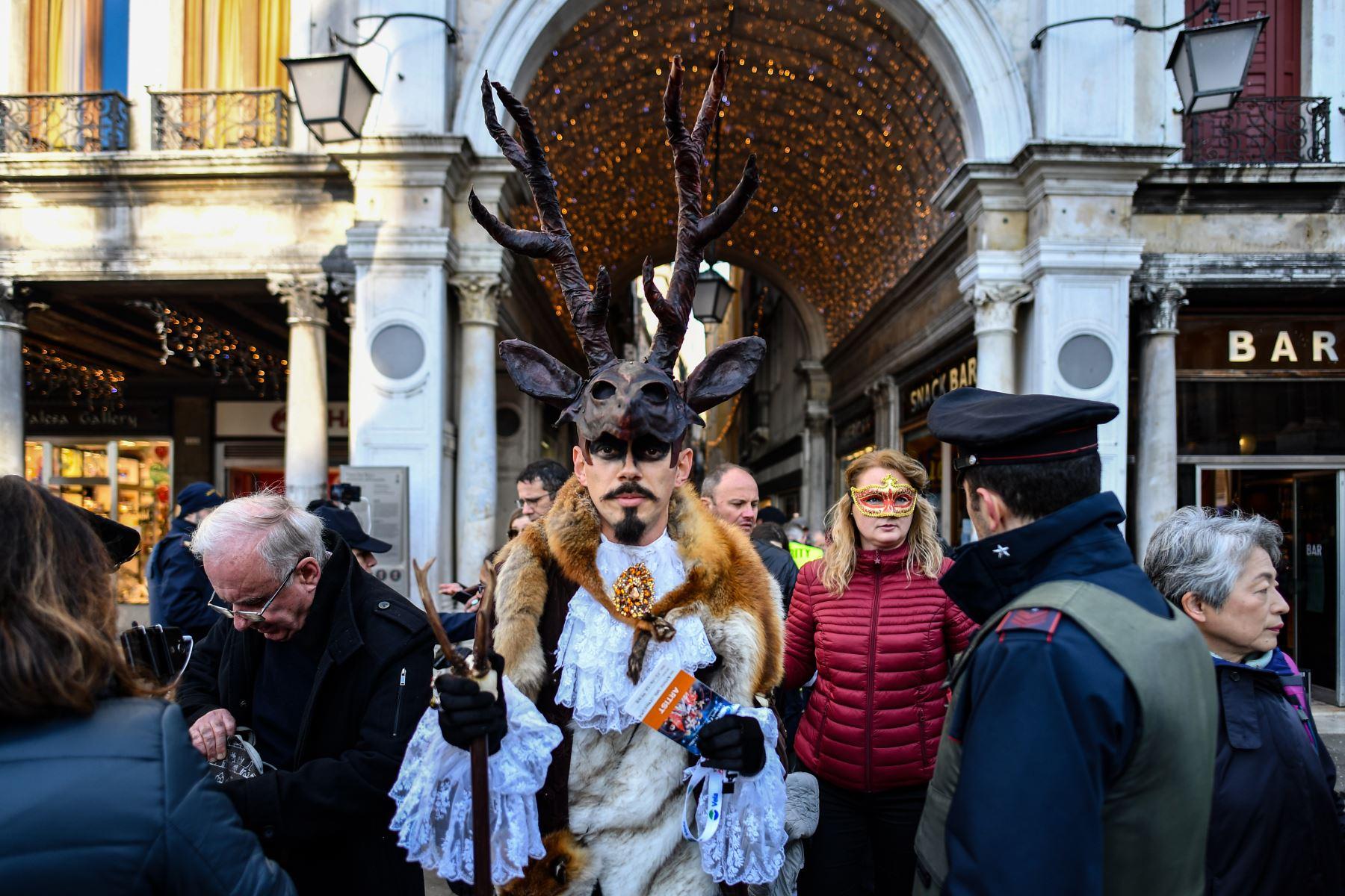 Un oficial de seguridad revisa a los participantes con máscaras y trajes de época que acceden a la Plaza de San Marcos durante el Carnaval de Venecia. Foto: AFP