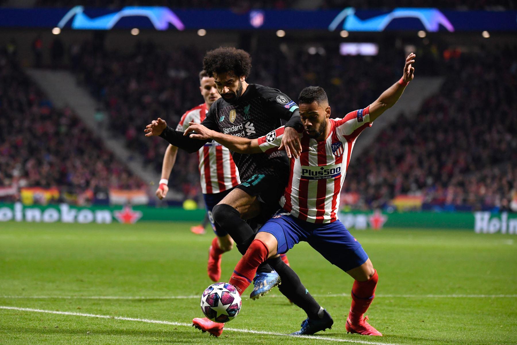 El defensor brasileño del Atlético de Madrid Renan Lodi (R) desafía al mediocampista egipcio de Liverpool Mohamed Salah durante la ronda de la UEFA Champions League, octavos de final-Foto:AFP`