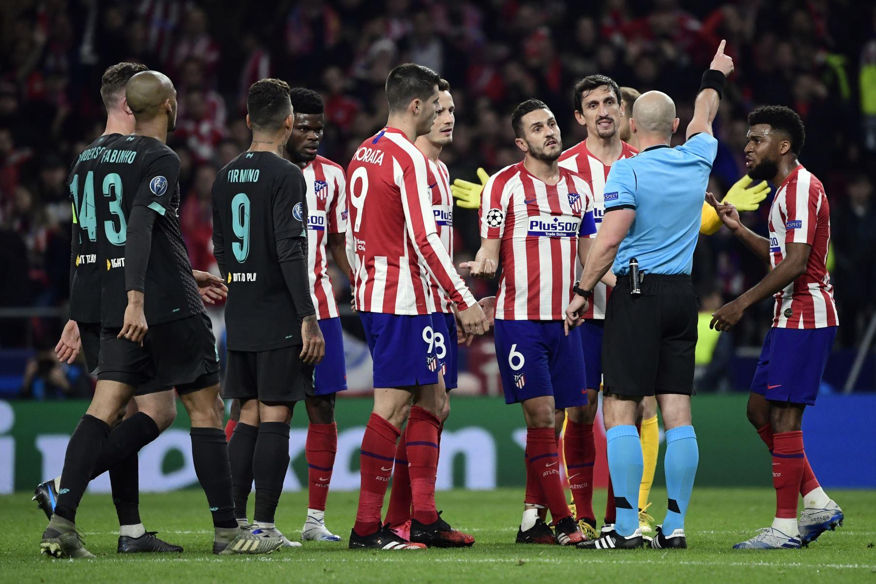 Los jugadores del Atlético de Madrid protestan ante el árbitro polaco Szymon Marciniak durante la UEFA Champions League, octavos de final.Foto:AFP