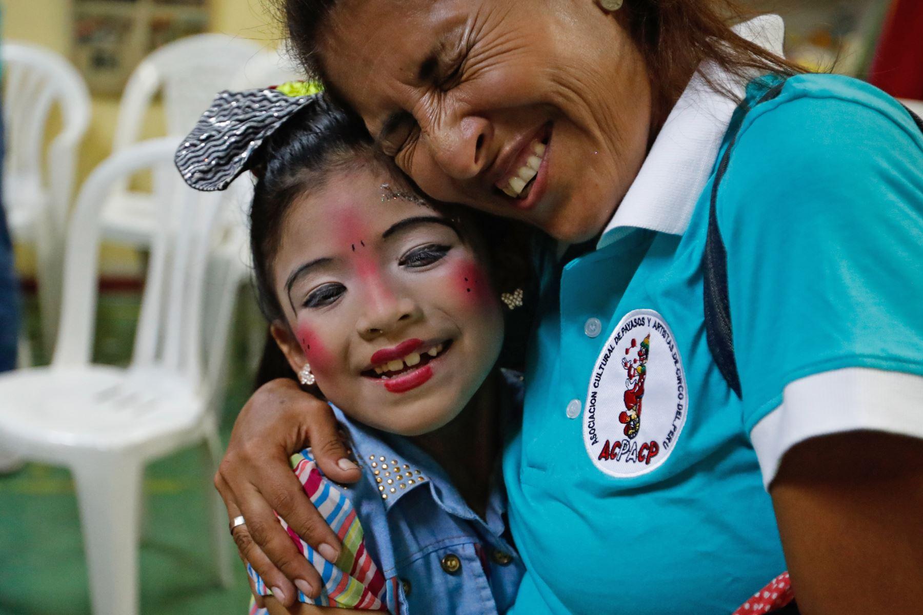 """La payasita """"Alfiler""""de 8 años recibe el abrazo de su madre """"Agujita"""" durante el homenaje a Ricardo Farfán, conocido en el ambiente artístico como el payaso """"Pitito"""" por sus 96 años. Foto: ANDINA/Carlos Lezama"""