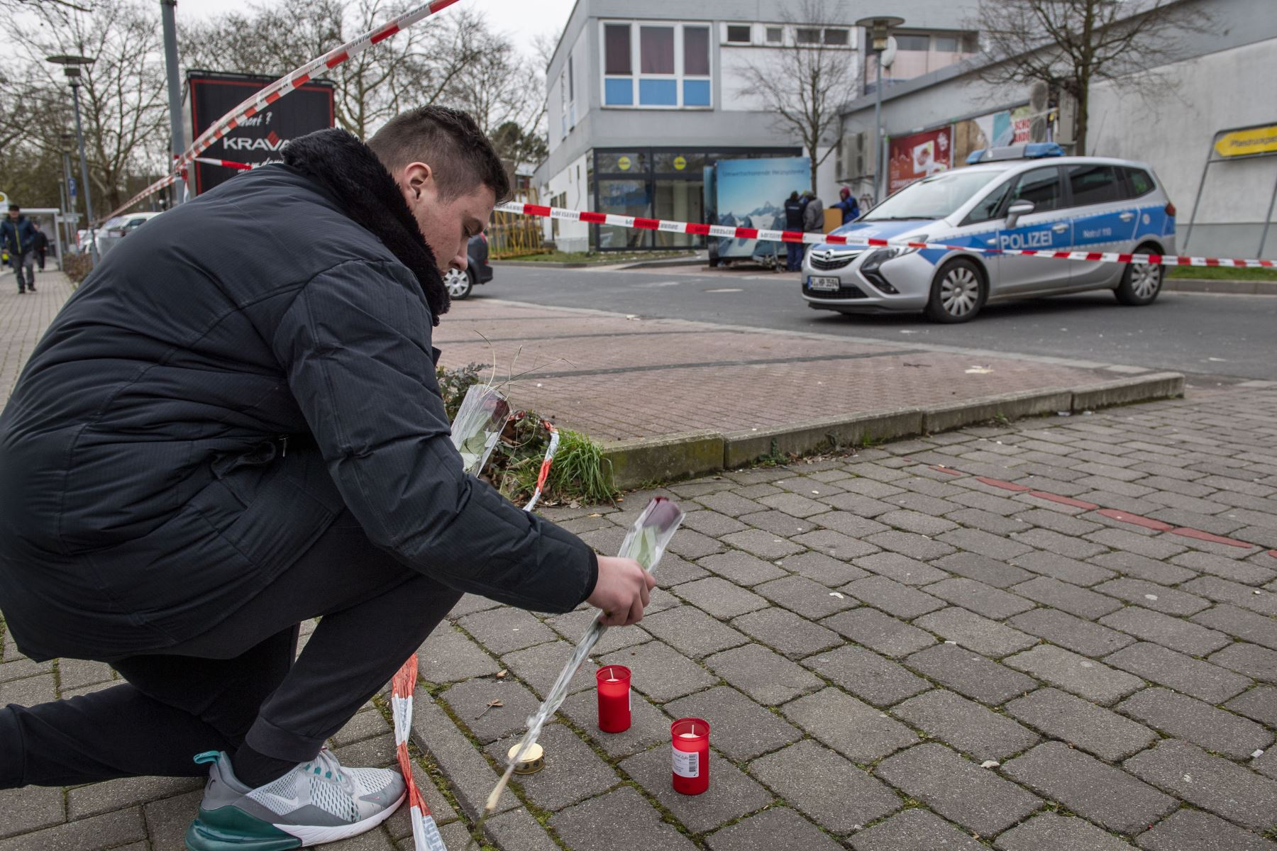 Un hombre pone velas y flores frente a uno de los locales atacados por un tiroteo en Kesselstadt, cerca de Frankfurt, Alemania occidental. Foto: AFP
