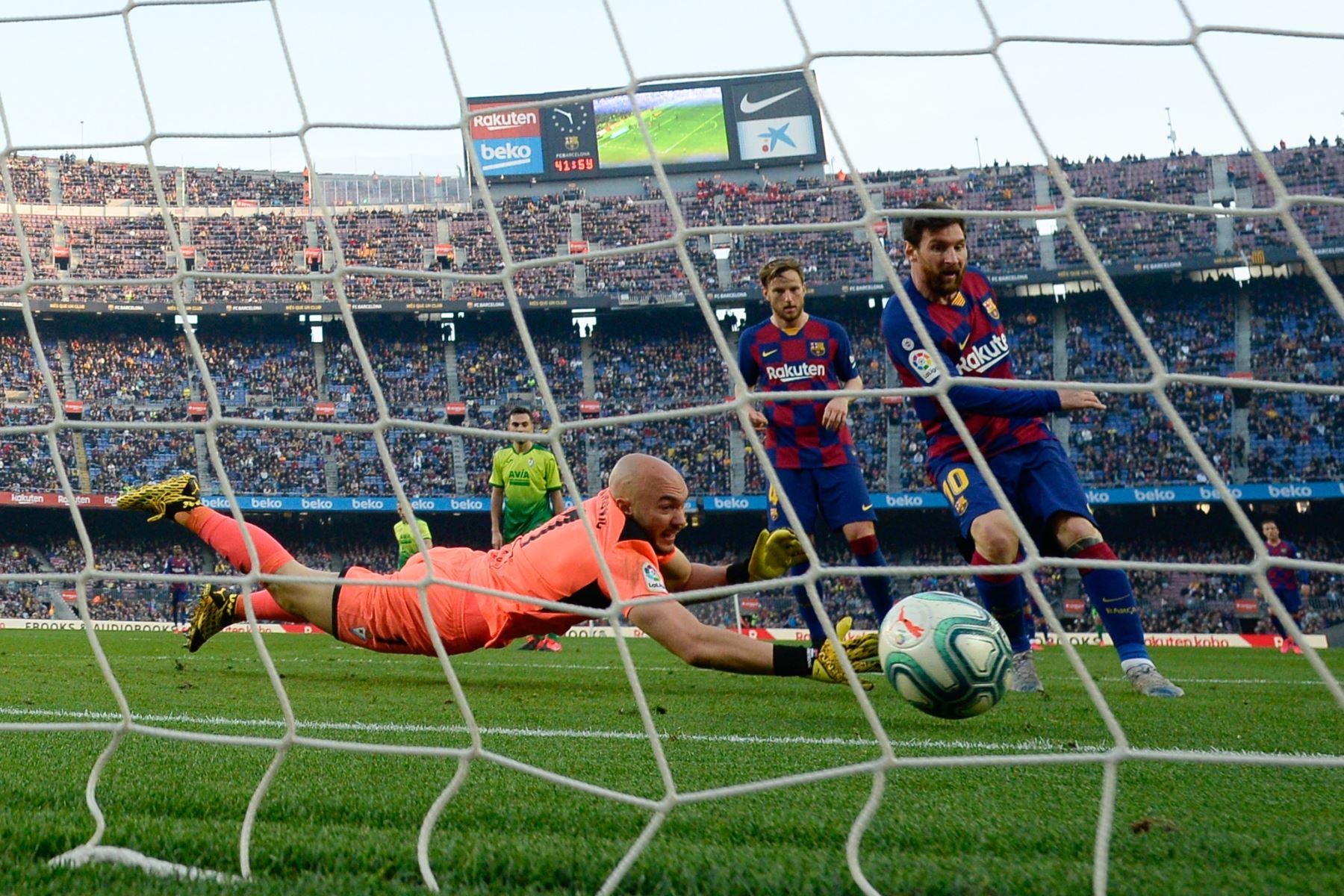 El delantero argentino de Barcelona Lionel Messi anota contra el portero serbio de Eibar Marko Dmitrovic durante el partido de fútbol de la liga española FC Barcelona contra SD Eibar. Foto: AFP