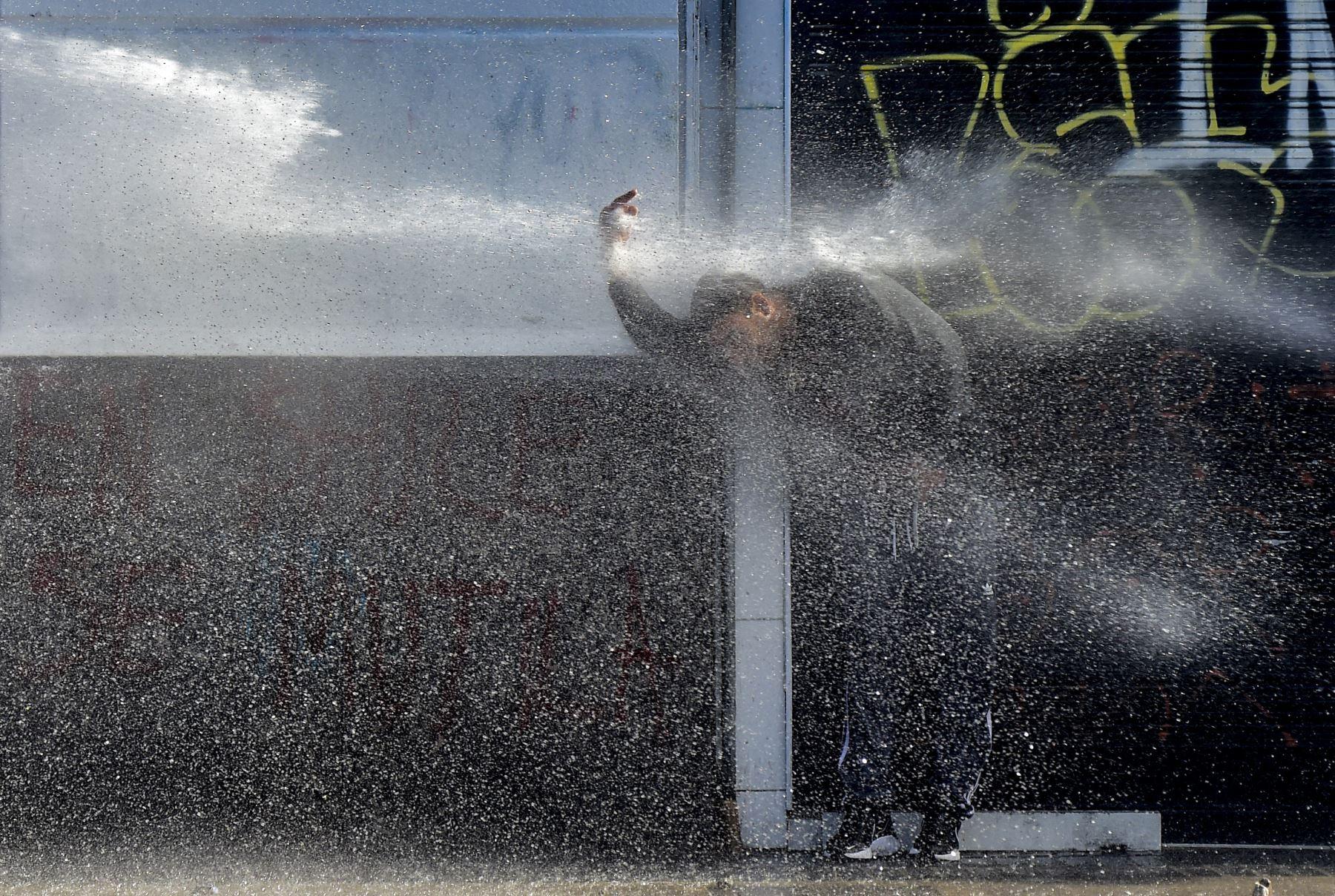 Un cañón de agua de la policía rocía a un manifestante durante una protesta contra el gobierno del presidente chileno Sebastián Piñera en Viña del Mar, durante el Festival de Música de Viña del Mar. AFP
