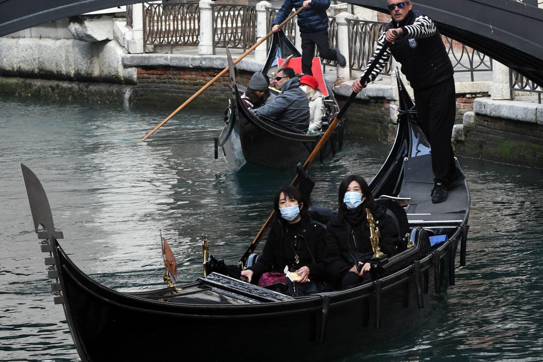 Turistas asiáticos que llevan máscaras protectoras viajan en una góndola en Venecia después de que el carnaval se canceló debido a un brote de coronavirus en Italia. Foto: AFP