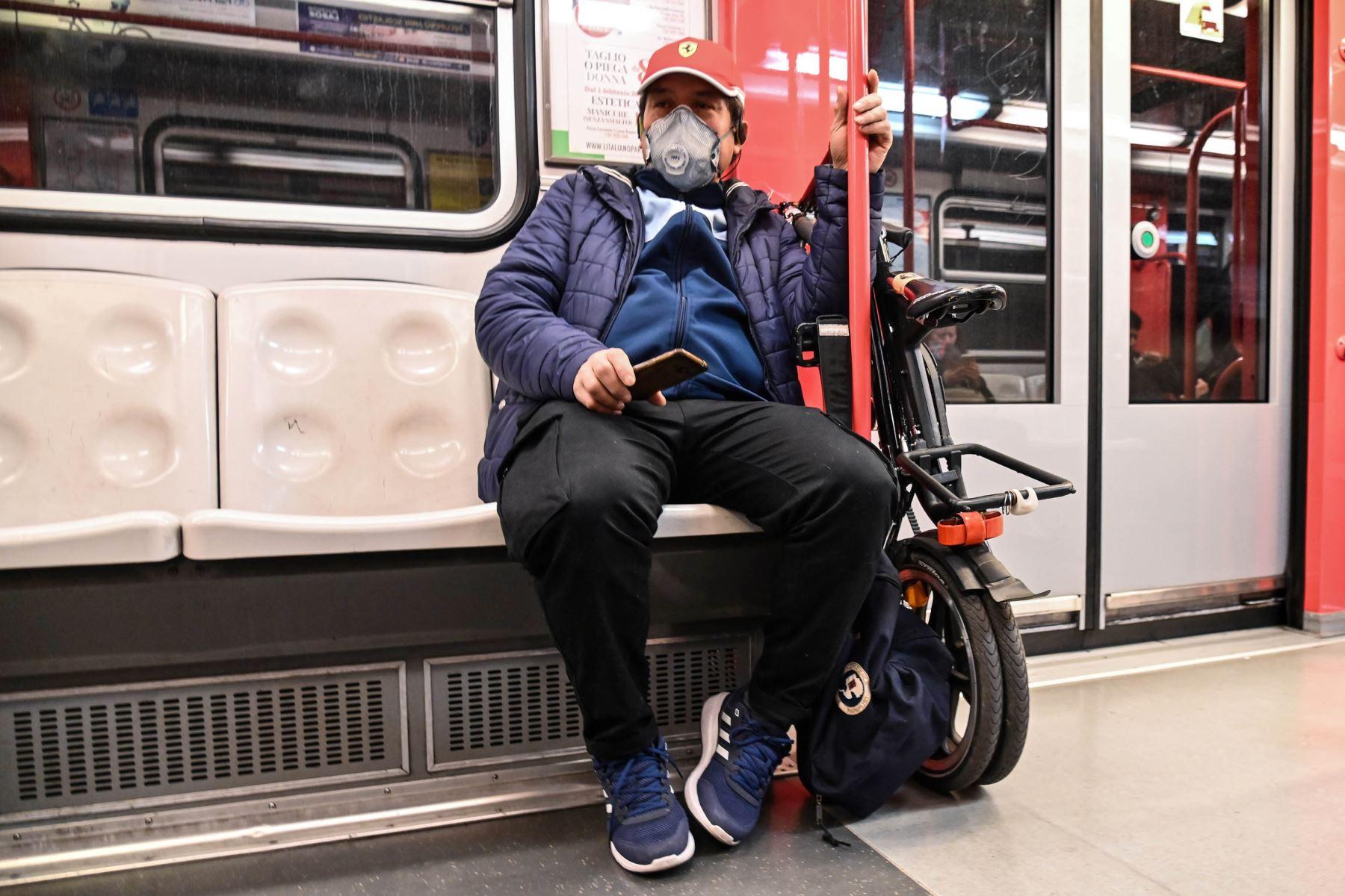 Un hombre que llevaba una máscara protectora se sienta en el metro, en el centro de Milán. Foto: AFP