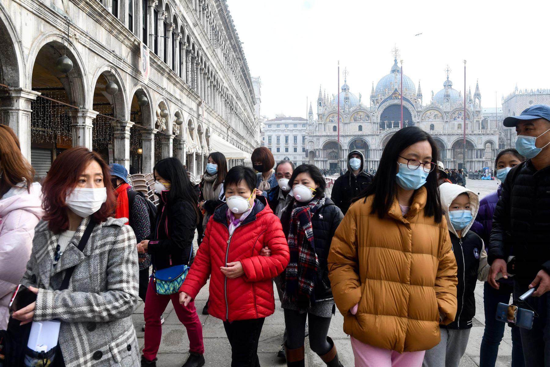 Turistas con máscaras protectoras visitan la Piazza San Marco, en Venecia. Foto: AFP