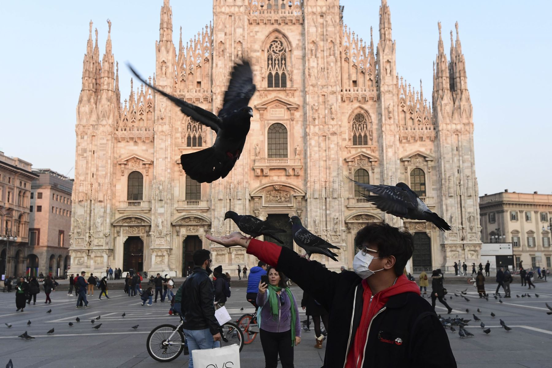 Un hombre con una máscara protectora juega con palomas en la Piazza del Duomo, en el centro de Milán, el 24 de febrero de 2020 tras las medidas de seguridad tomadas en el norte de Italia contra el COVID-19, el nuevo coronavirus. Foto: AFP