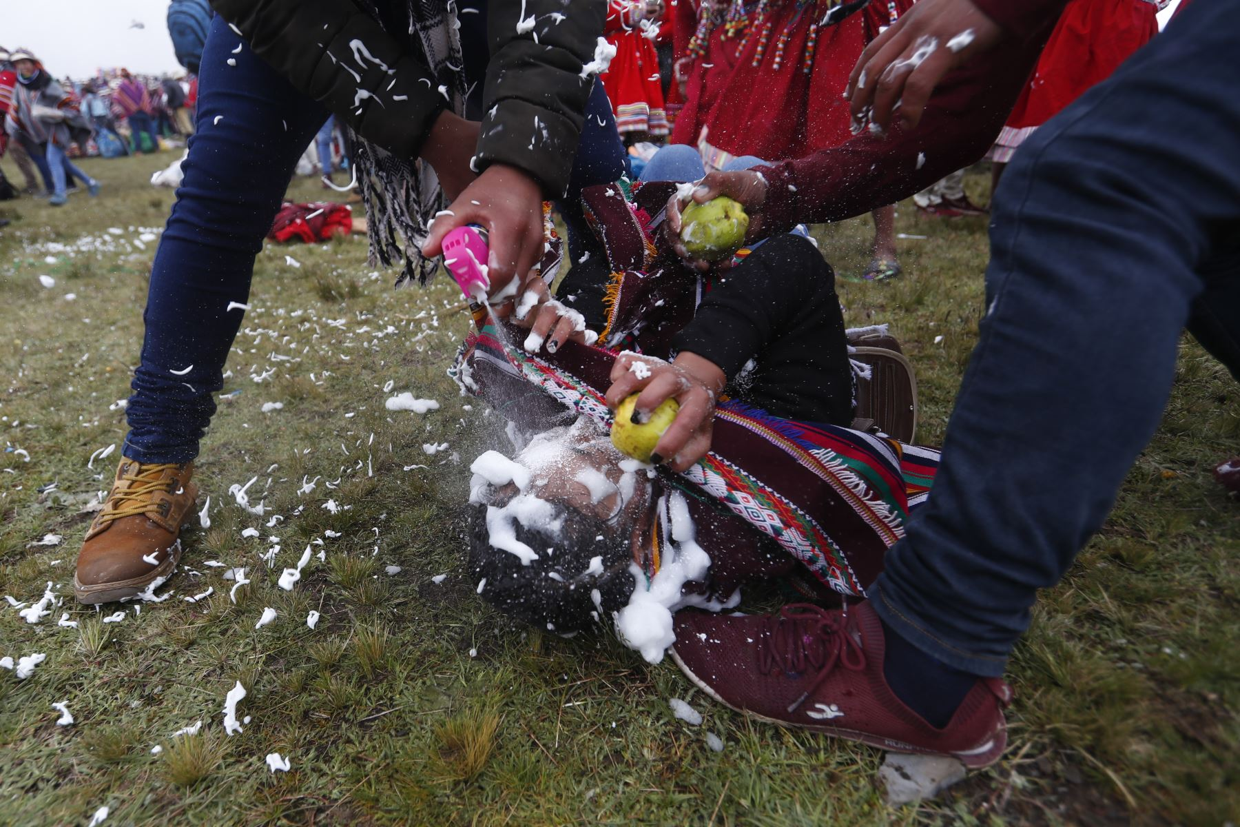 Dos jóvenes logran tumbar a una alegre muchacha quien venía lanzando espuma a diestra y siniestra contra ellos. Foto: ANDINA/Renato Pajuelo