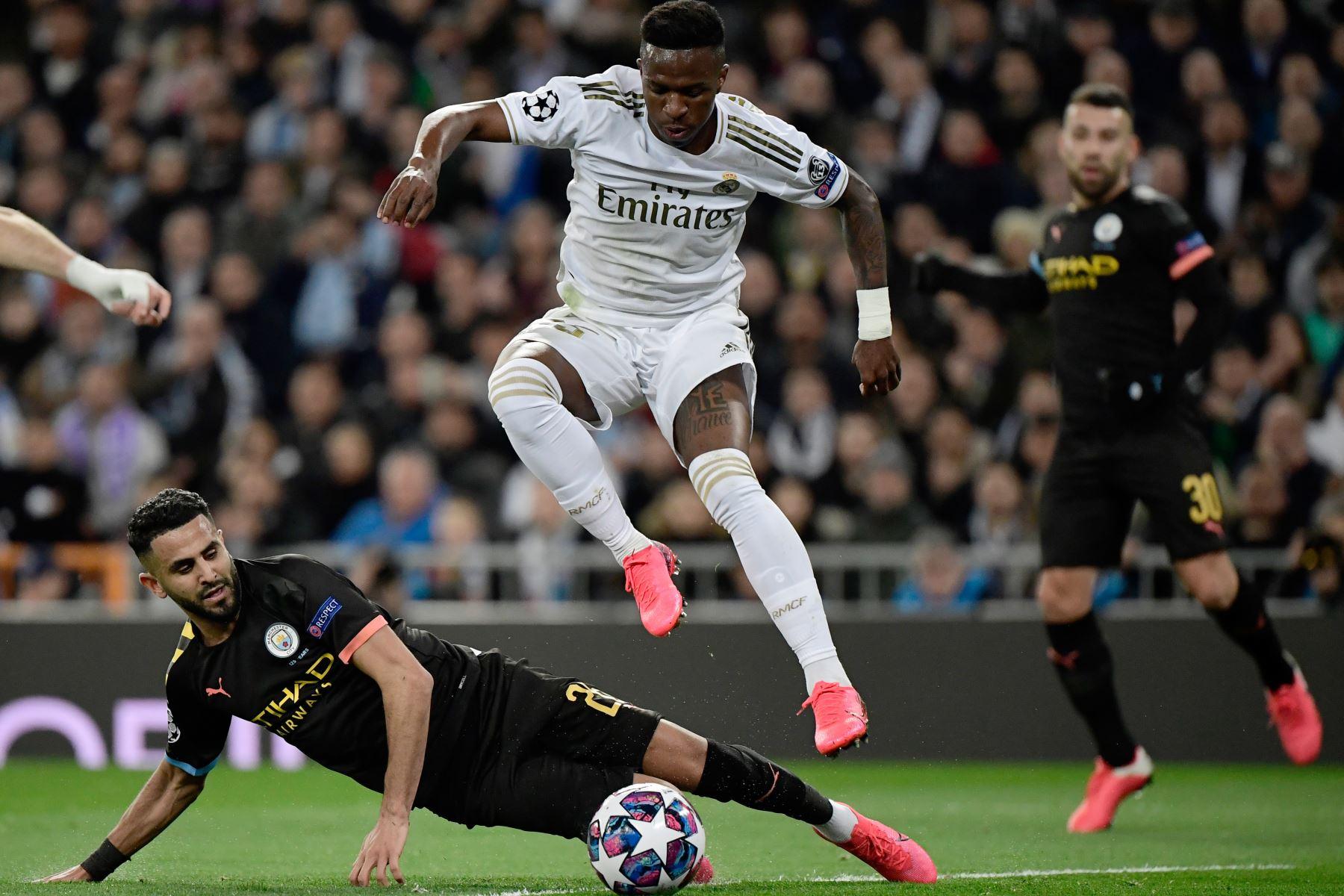 El delantero brasileño del Real Madrid, Vinicius Junior, salta sobre el centrocampista argelino del Manchester City, Riyad Mahrez, durante la ronda de 16 de la UEFA Champions League entre el Real Madrid CF y el Manchester City. Foto: AFP