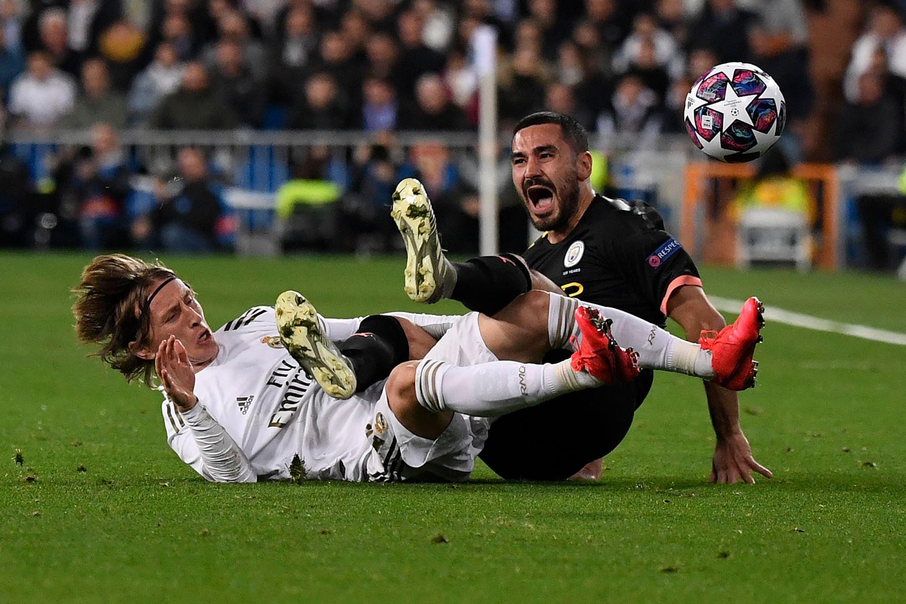 El centrocampista croata del Real Madrid Luka Modric  cae con el centrocampista alemán del Manchester City Ilkay Gundogan durante la ronda de 16 partidos de fútbol de ida de la Liga de Campeones de la UEFA entre el Real Madrid CF y el Manchester City. Foto: AFP