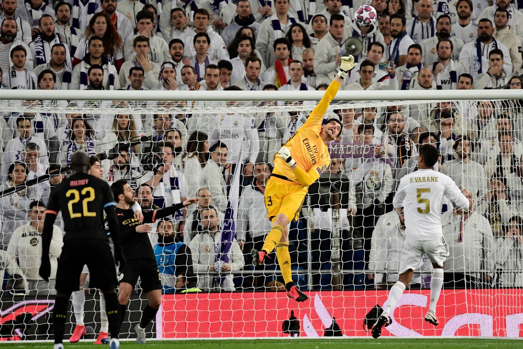 El portero belga del Real Madrid, Thibaut Courtois, despeja el balón durante la ronda de 16 partidos de fútbol de ida de la UEFA Champions League entre el Real Madrid CF y el Manchester City. Foto: AFP