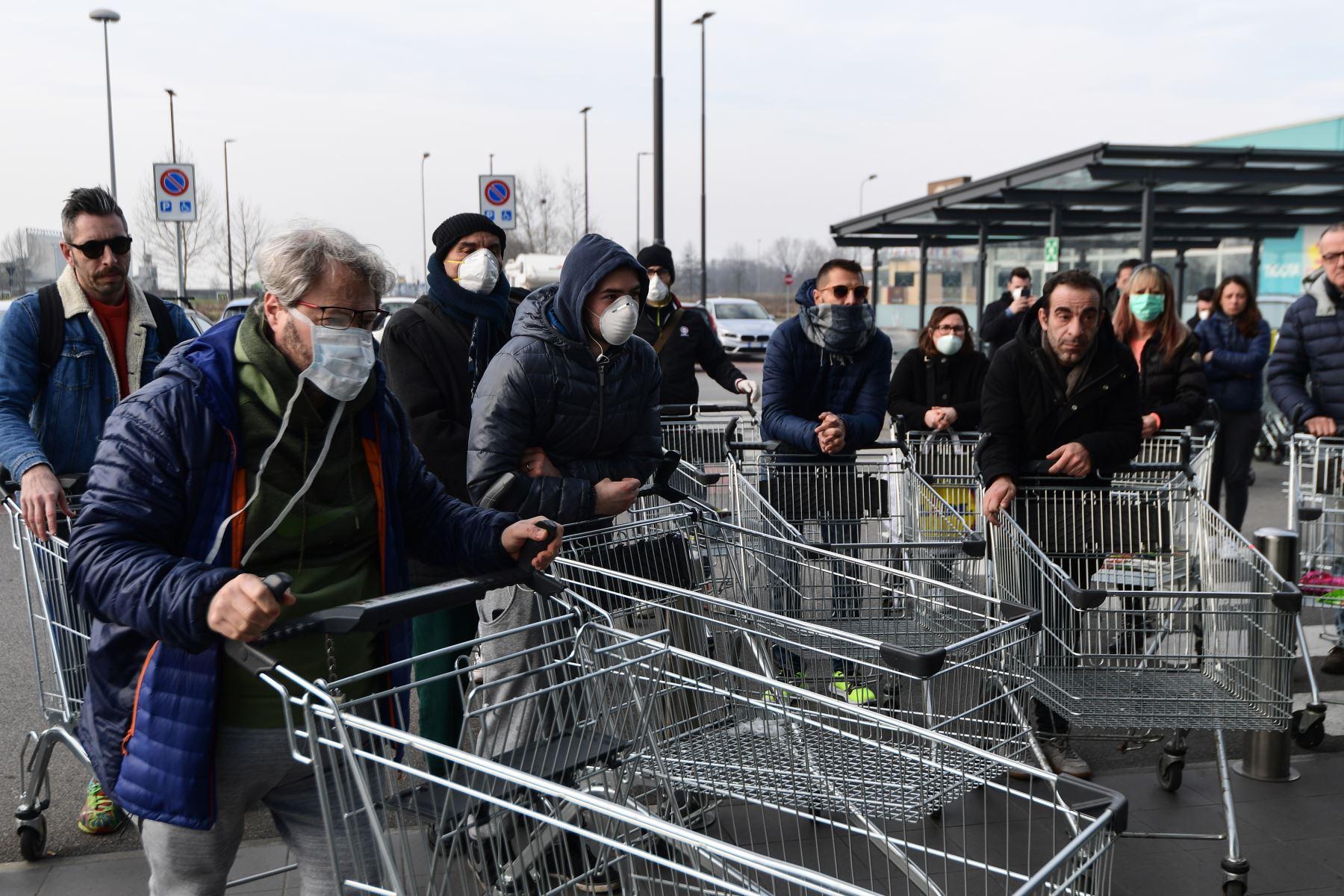 Los residentes esperan tener acceso a comprar en un supermercado en pequeños grupos de cuarenta personas  en la  ciudad italiana de Casalpusterlengo, a la sombra de un nuevo brote de coronavirus, mientras Italia tomó medidas drásticas de contención a medida que el mundo teme por el epidemia en espiral. AFP