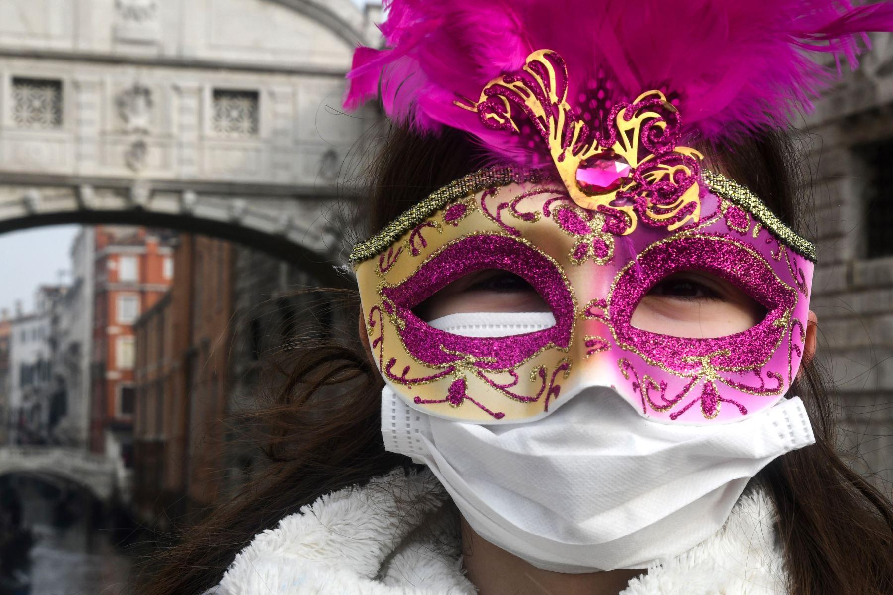 Un joven turista con una máscara protectora y una máscara de Carnaval visita las calles de Venecia. AFP