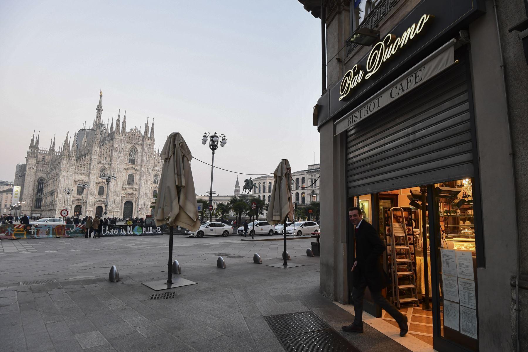 Un hombre sale de un bar al lado de la Piazza del Duomo en el centro de Milán que cierra a las 6 p.m.  luego de tomar medidas de seguridad en el norte de Italia contra el COVID-19. AFP