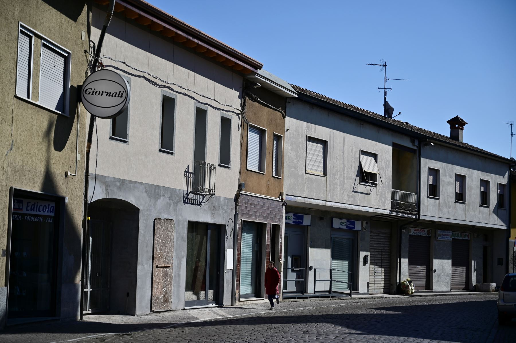 Una mujer pasa por las tiendas cerradas a lo largo de la calle principal de Secugnano, el pueblo más cercano a Zorlesco, al sureste de Milán,que se encuentra en la zona roja del COVID-19, el nuevo brote de coronavirus en el norte de Italia. AFP