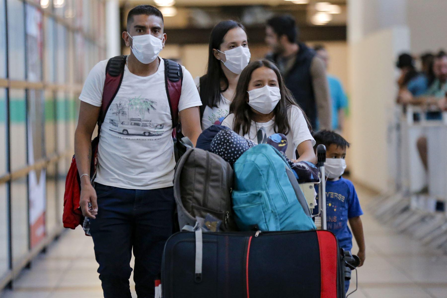 Pasajeros caminan con máscaras protectoras como medida preventiva contra la propagación del coronavirus COVID-19, en el Aeropuerto de Santiago de Chile. Foto: AFP