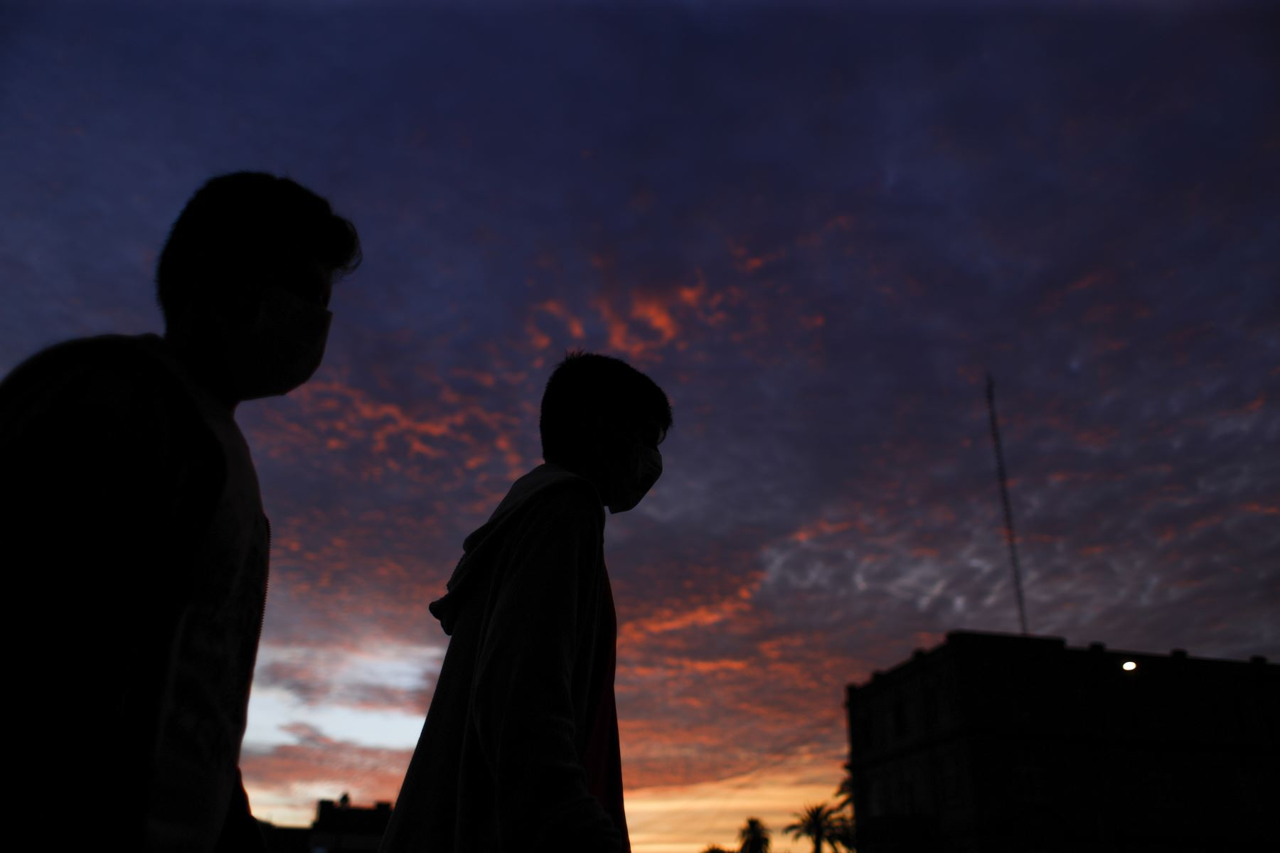 Jóvenes caminan con mascarilla al caer la tarde en el Centro de Lima. Foto: ANDINA/Renato Pajuelo