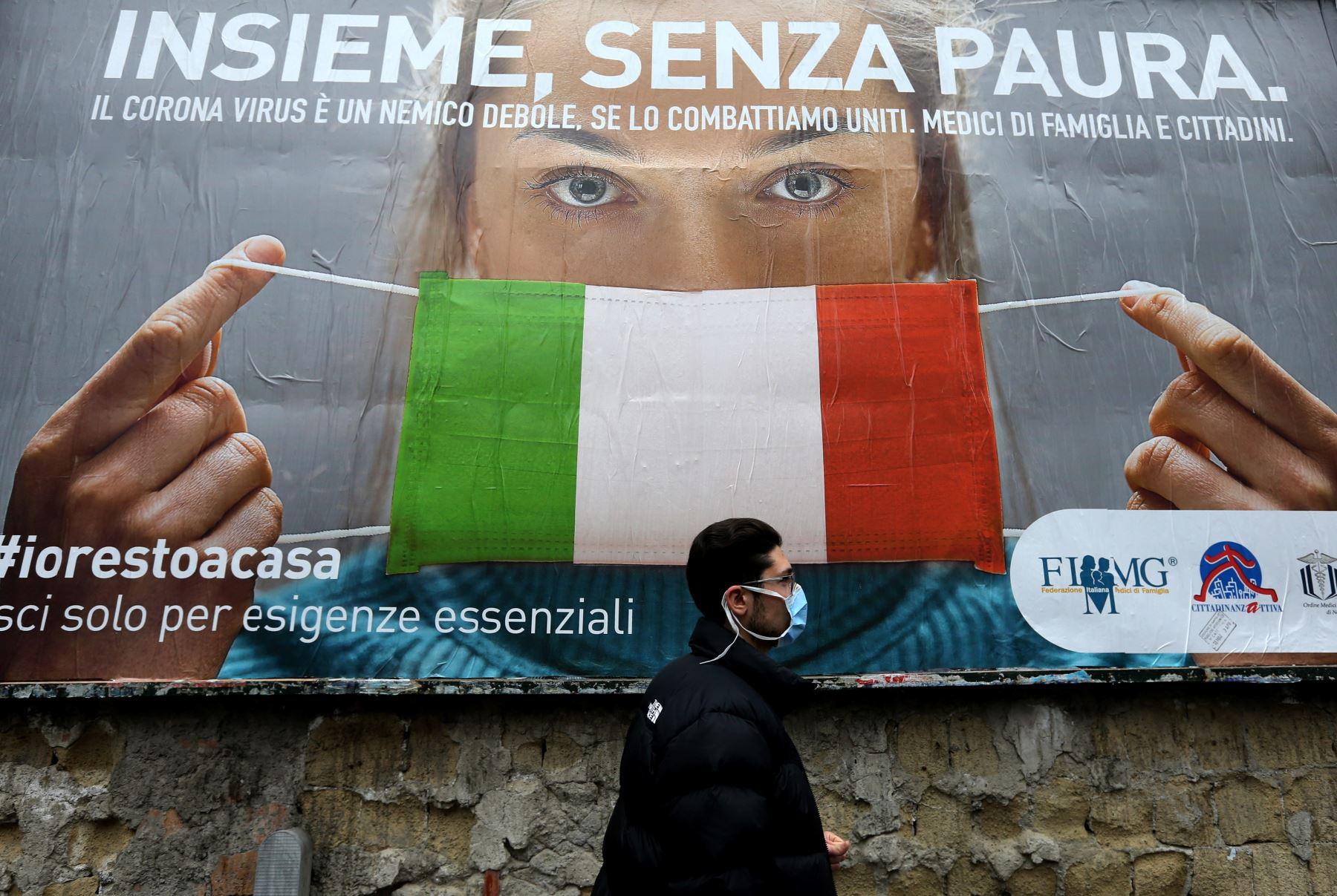 Un hombre pasa junto a una gran valla publicitaria para dar a conocer las medidas tomadas por el gobierno italiano para luchar contra la propagación del covid-19 en Nápoles, Italia. Foto: AFP