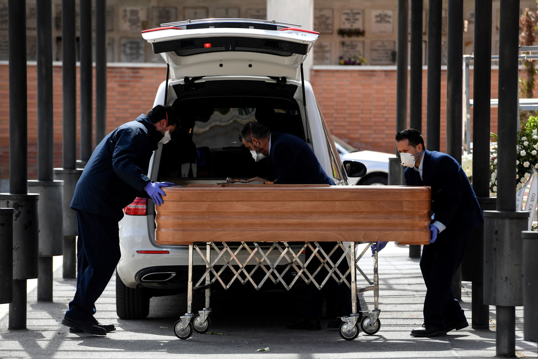 Los empleados de la funeraria con máscaras faciales llevan un ataúd al crematorio del cementerio de La Almudena en Madrid durante el funeral de una víctima del coronavirus COVID-19. España ha sido uno de los países más afectados, registrando el tercer mayor número de muertes con las últimas cifras que muestran un total de 2,696. Foto: AFP