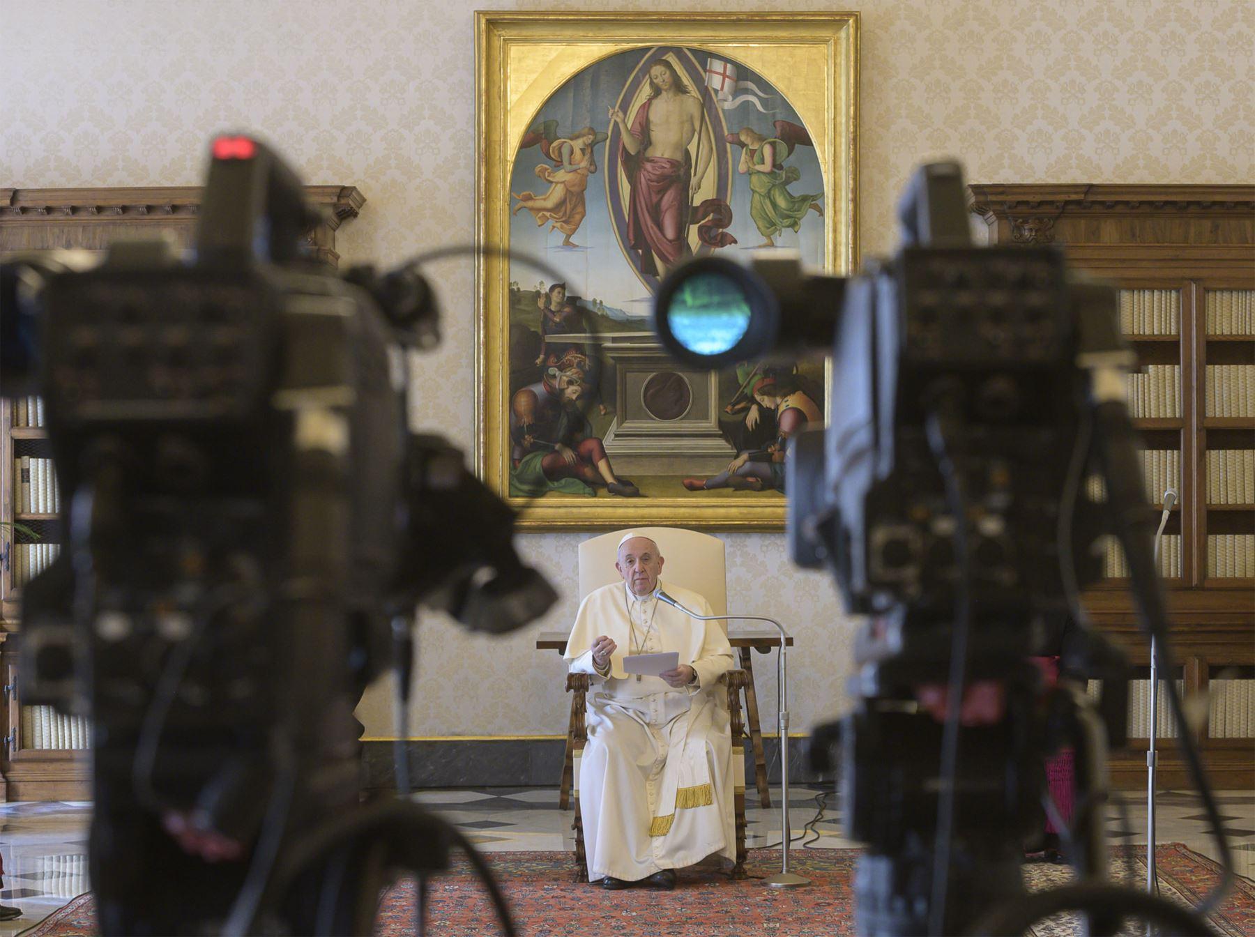 """Papa Francisco recitando la oración """"Padre Nuestro"""" durante una transmisión en vivo desde la biblioteca del palacio apostólico en el Vaticano durante el encierro luego de la nueva pandemia de coronavirus COVID-19. Foto: AFP"""