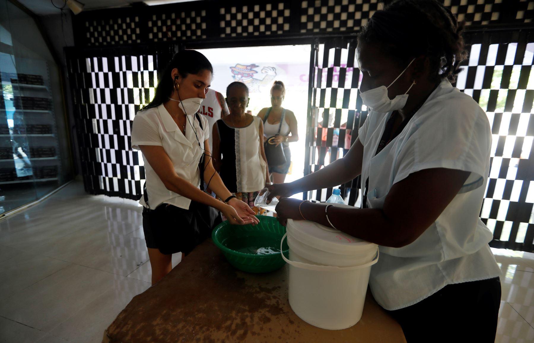 Varias personas hacen fila para el lavado de manos para poder ingresar a un centro comercial en La Habana, Cuba. Foto: EFE