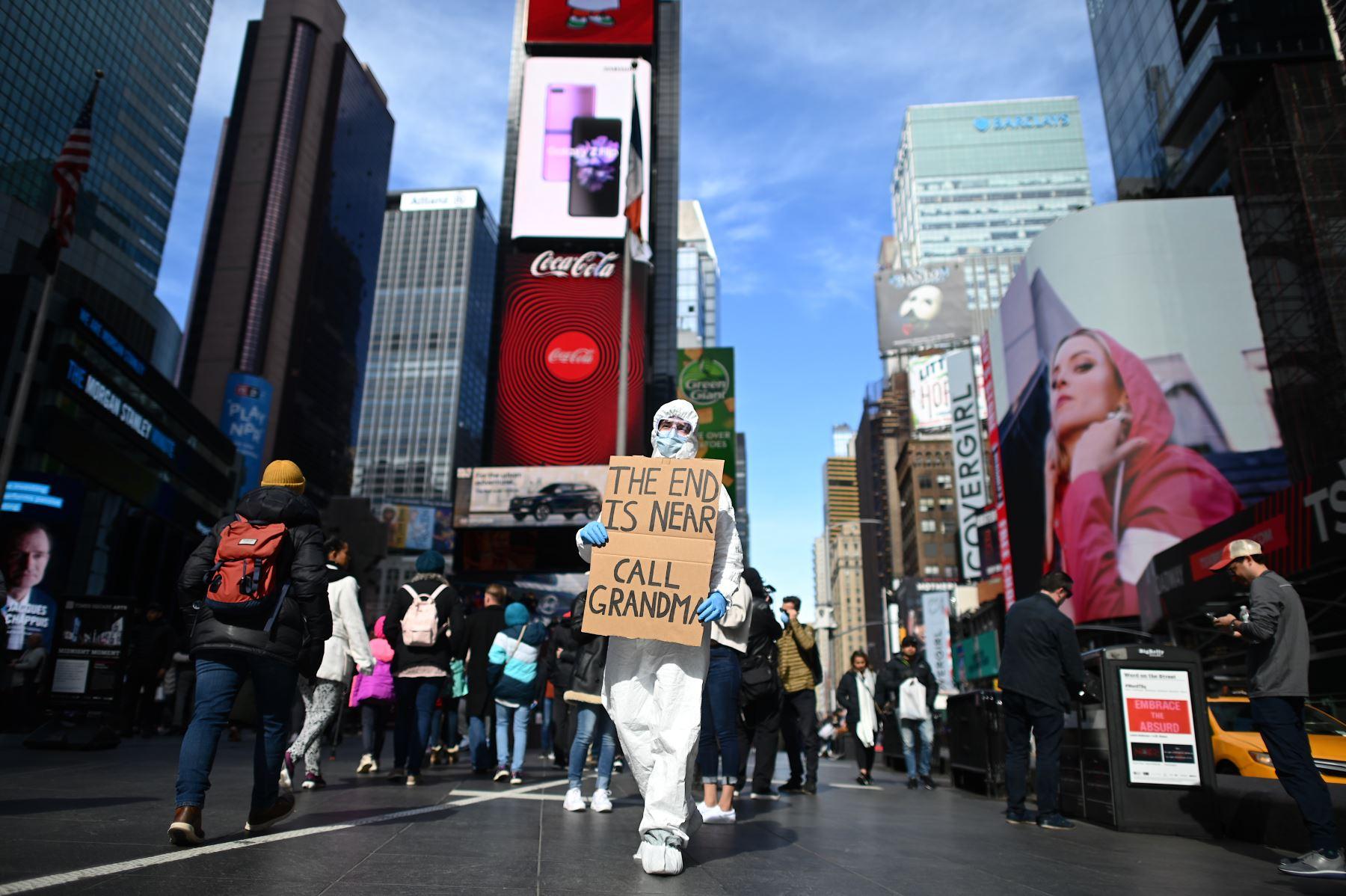 """Un hombre vestido con un traje de materiales peligrosos y una máscara sostiene un cartel que dice """"el final está cerca de llamar a la abuela"""" en Times Square  en la ciudad de Nueva York. AFP"""