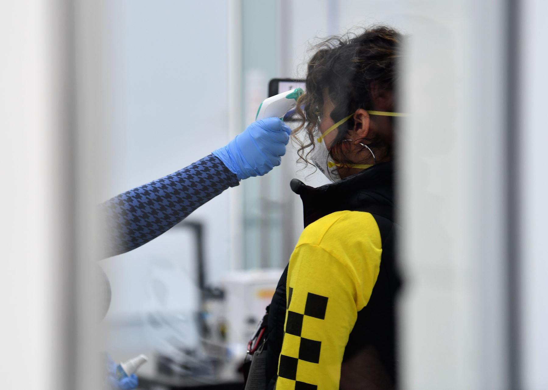 Un periodista mide su temperatura cuando el alcalde de la ciudad de Nueva York, Bill de Blasio, visita el Brooklyn Navy Yard, donde las empresas industriales locales han comenzado a fabricar equipos de protección personal (EPP) como protectores faciales para abastecer a los trabajadores de la salud y hospitales de New York. AFP