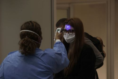 Profesionales de vigilancia sanitaria miden la temperatura a los pasajeros y tripulantes que desembarcan en el Aeropuerto Internacional de Galeão, en Río de Janeiro (Brasil). Foto: EFE