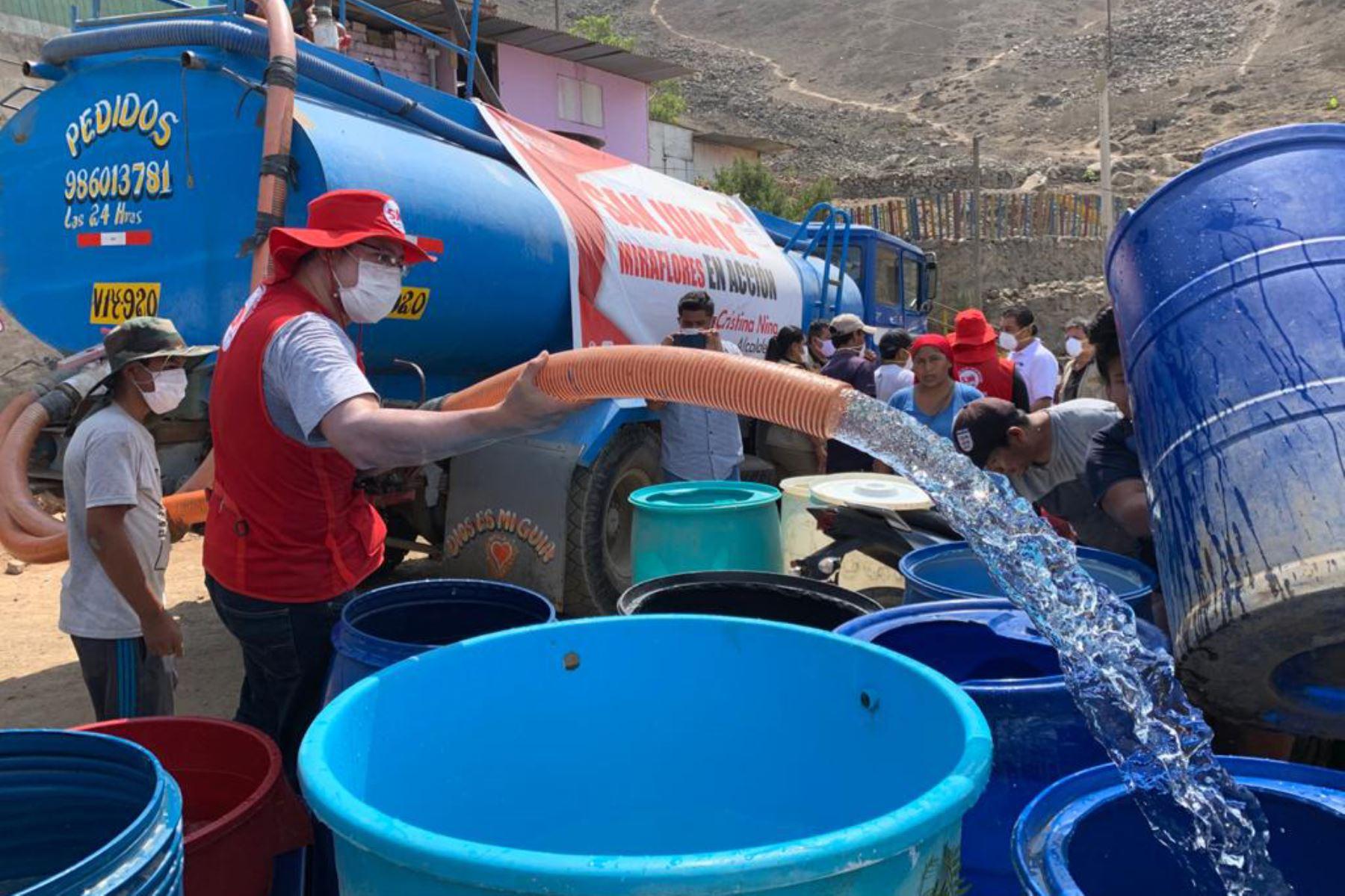 El ministro de Vivienda Rodolfo Yanez y la alcaldesa distrital Cristina Nina de San Juan de Miraflores abastecen de agua en el A.H. Flor de Amancaes. Foto: Ministerio de Vivienda