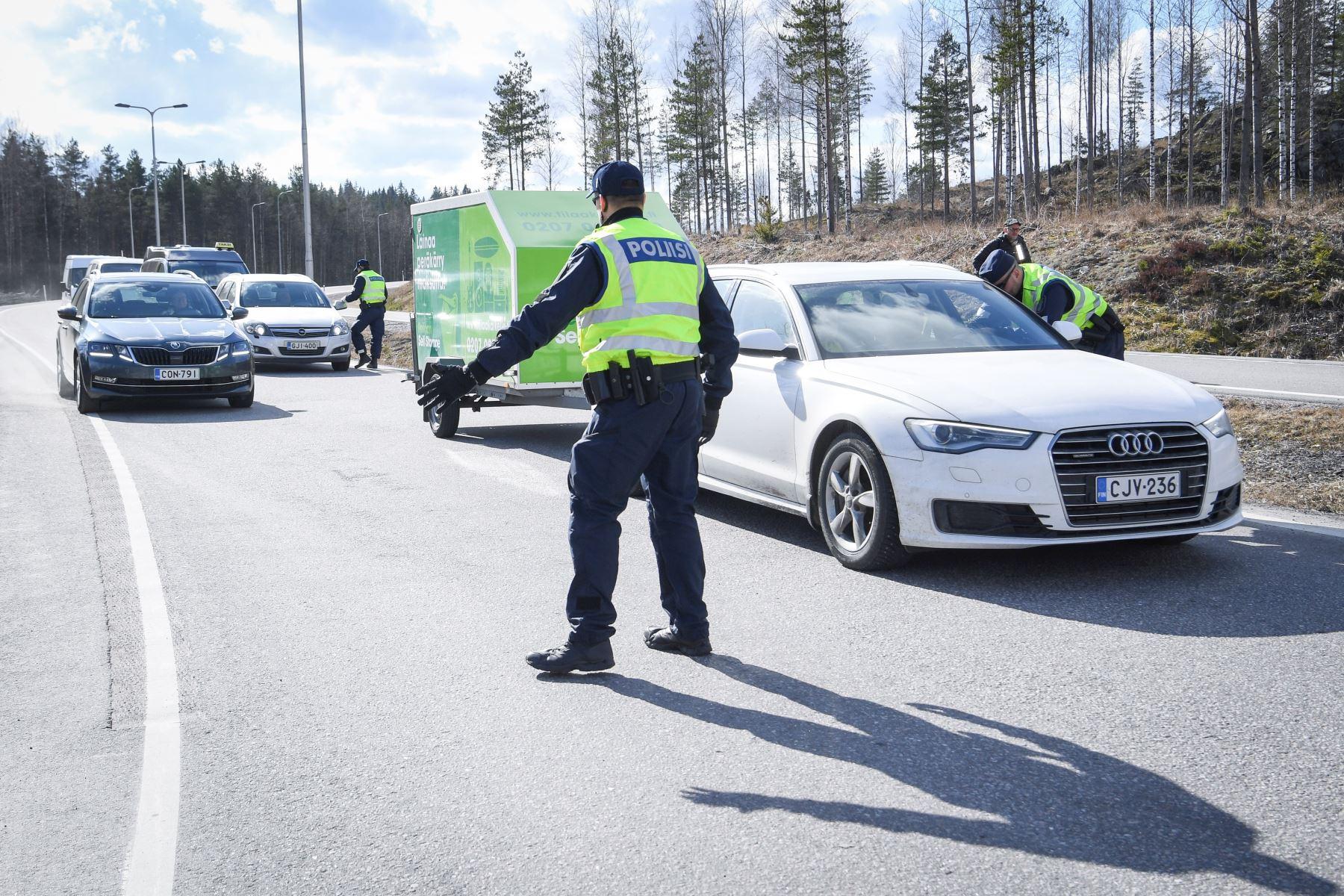Un oficial de policía interactúa con un conductor en un puesto de control en la autopista E75, que conecta Helsinki y Lahti, en Orimattila, Finlandia. Foto: EFE
