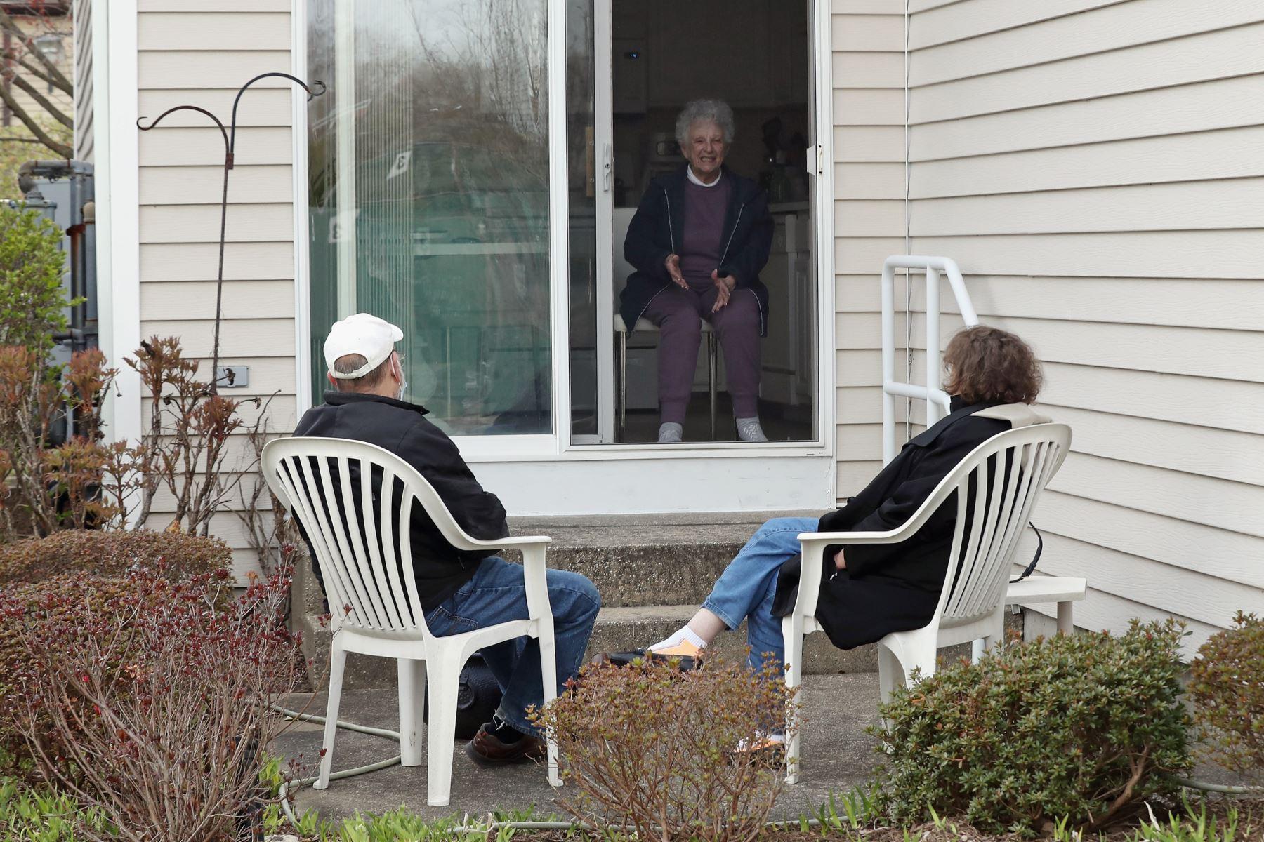 Un yerno y una hija visitan a su madre mientras practican el distanciamiento social en un complejo de viviendas para personas mayores en East Meadow, Nueva York. Foto: AFP
