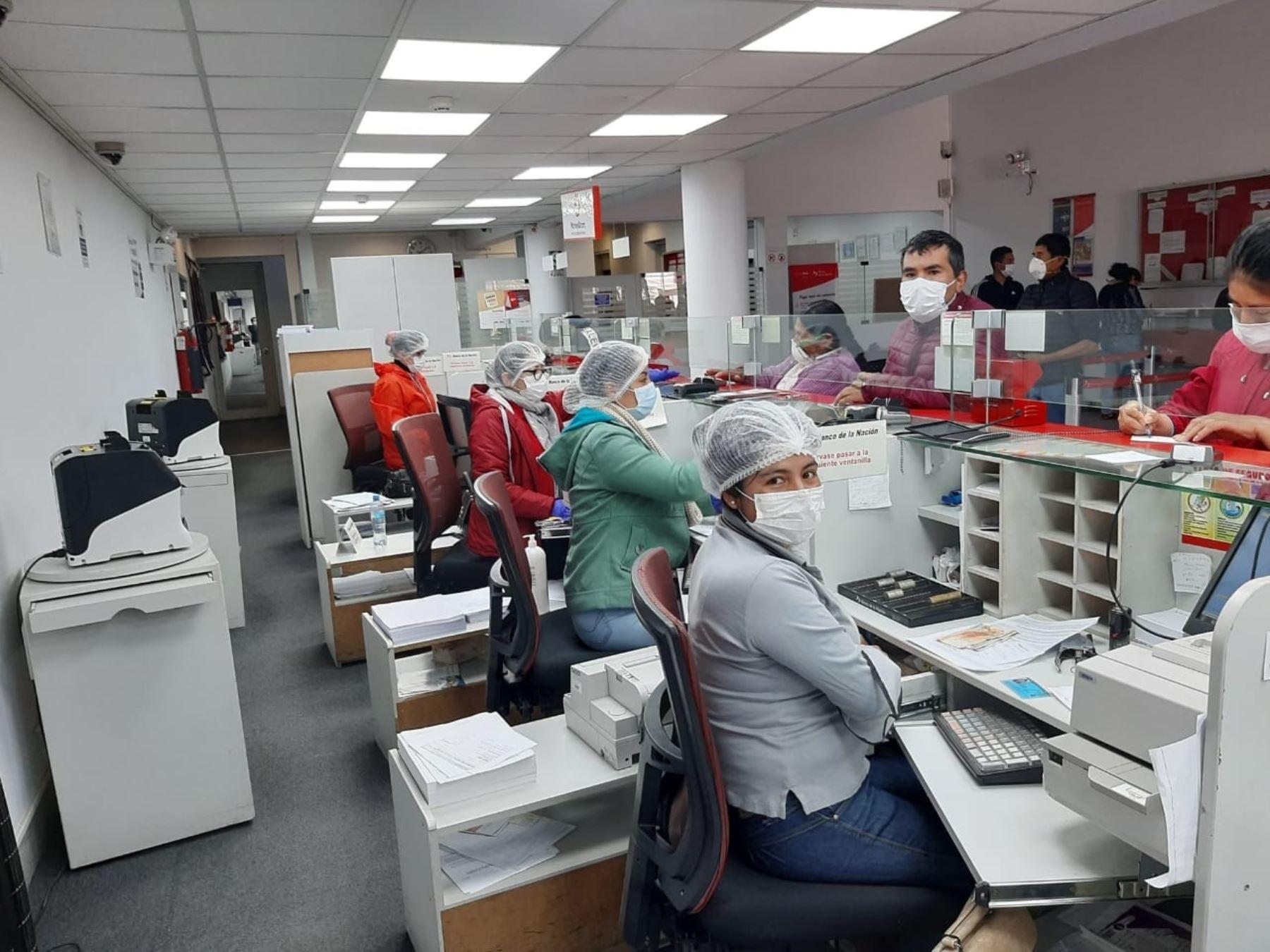 Trabajadores del Banco de la Nación, que atienden de manera personal al público, usan mascarillas de protección. Foto: Difusión