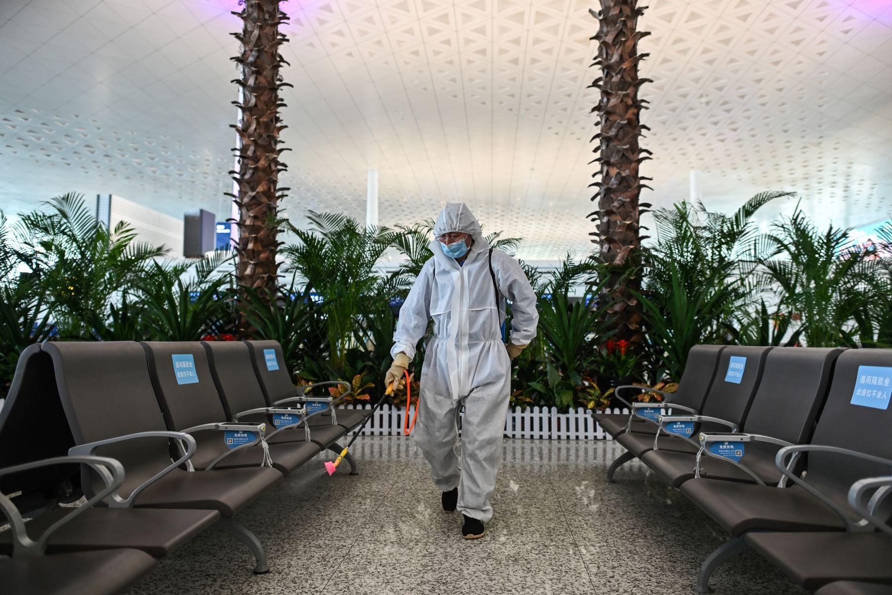 Un trabajador que usa equipo de protección rocía desinfectante en el aeropuerto de Tianhe después de su reapertura hoy, en Wuhan. Foto: AFP