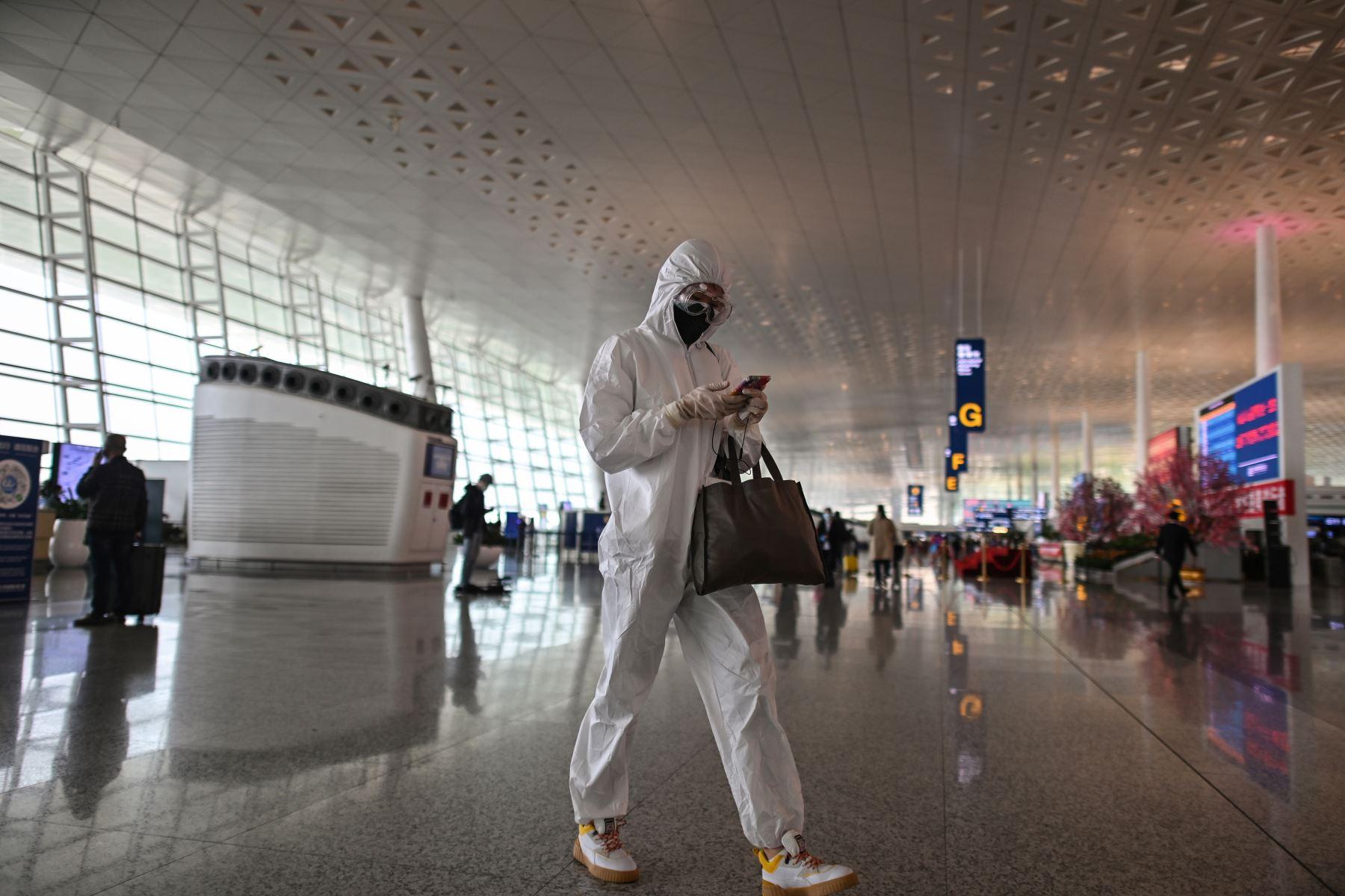Un pasajero que usa equipo de protección camina en el aeropuerto de Tianhe después de que fue reabierto hoy, en Wuhan, en la provincia central de Hubei, China. Foto: AFP