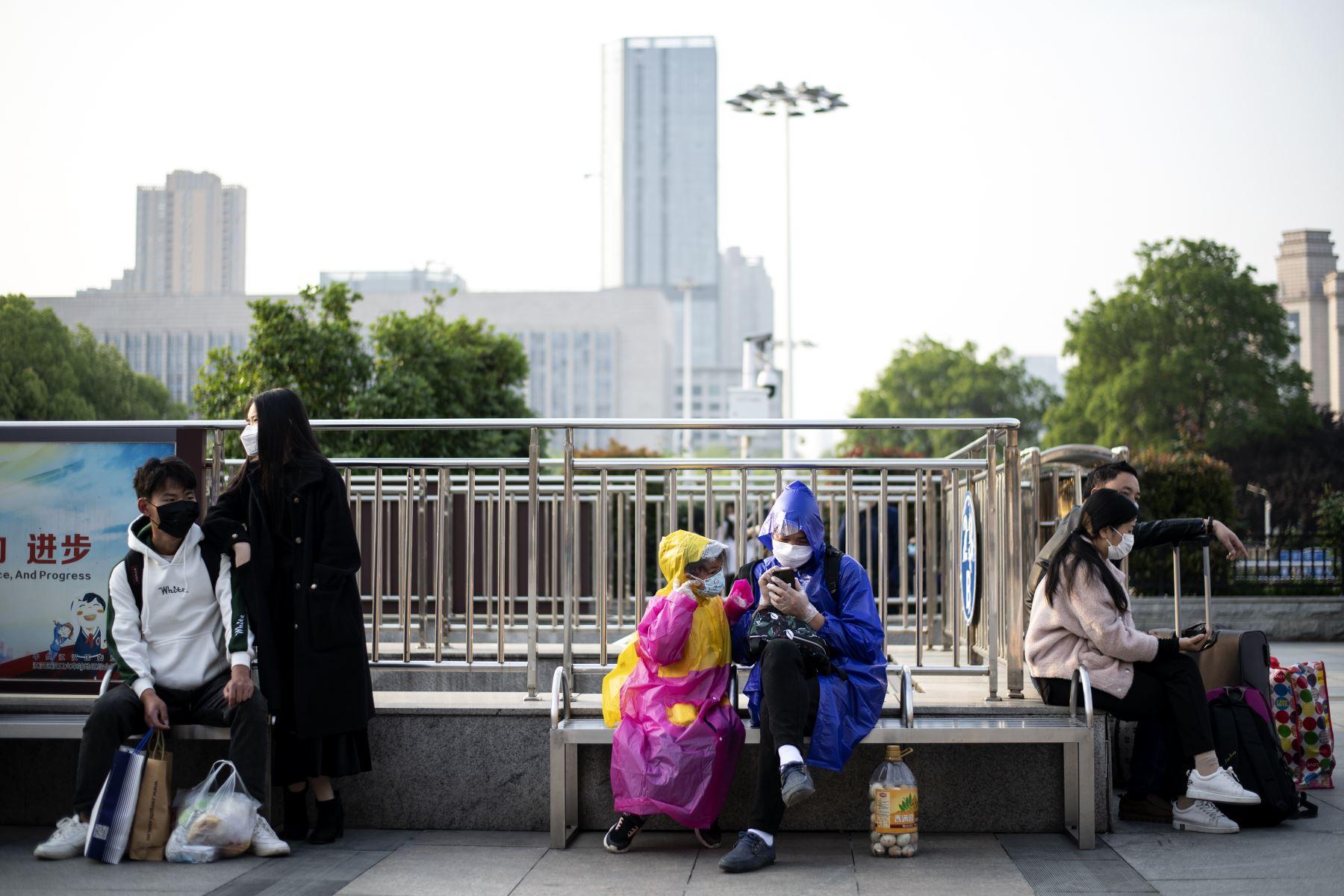 Las personas con máscaras faciales se sientan frente a la estación de tren de Hankou en Wuhan cuando llegan con la esperanza de tomar uno de los primeros trenes que salen de la ciudad. Foto: AFP
