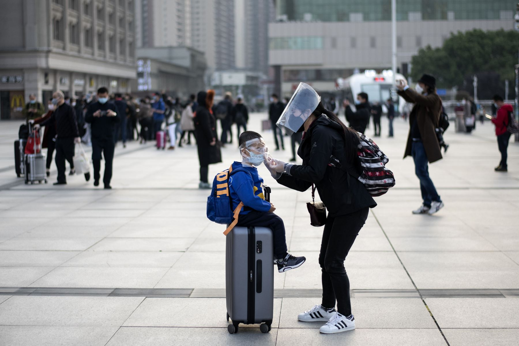 Una mujer con una máscara facial ajusta la máscara de su hijo cuando llegan a la estación de tren de Hankou en Wuhan para tomar uno de los primeros trenes que salen de la ciudad. Foto: AFP